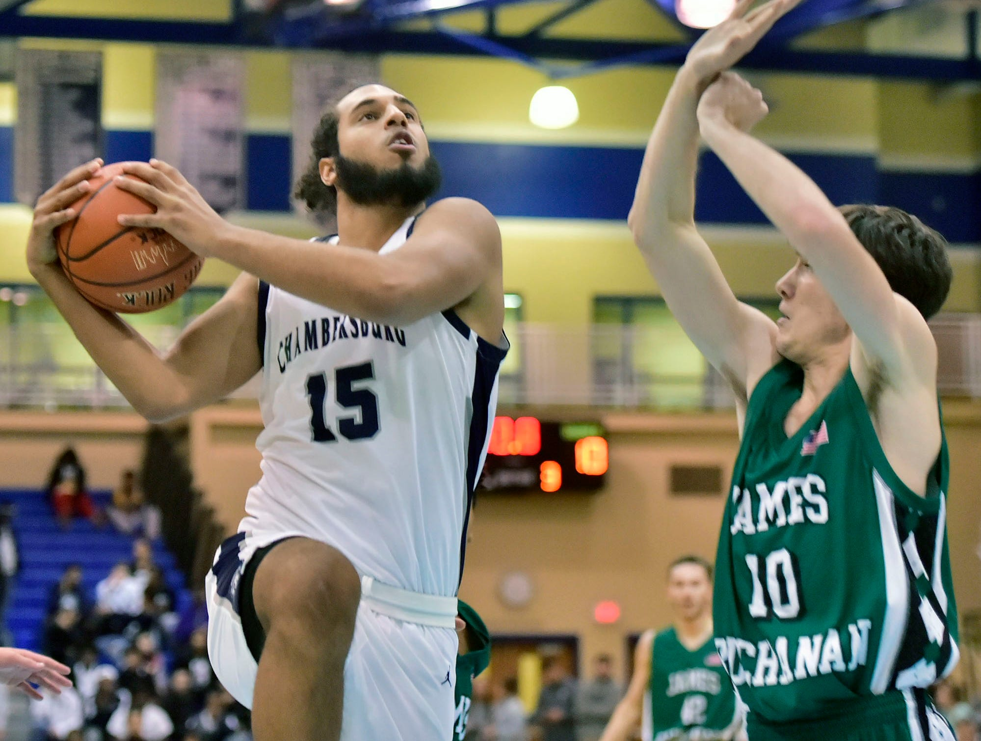 Chambersburg's Tyler Collier (15) drives to the basket as JAmes Buchanan's Dan Corcoran (10) defends.  Chambersburg played James Buchanan boys during the Franklin County Tip-Off Tournament, Friday, Dec. 7, 2018.