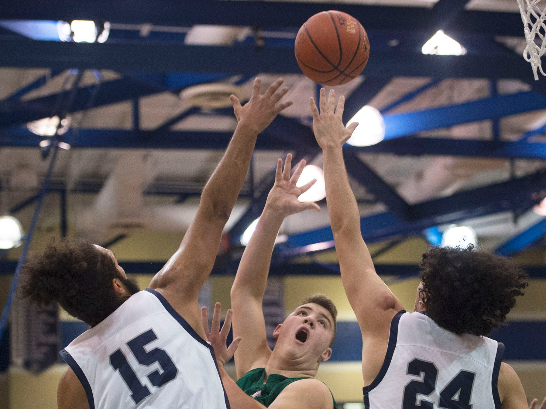 James Buchanan's Colton Hartman tries a hook shot over Chambersburg's Tyler Collier (15) and Ty Holsopple (24). Chambersburg played James Buchanan boys during the Franklin County Tip-Off Tournament, Friday, Dec. 7, 2018.