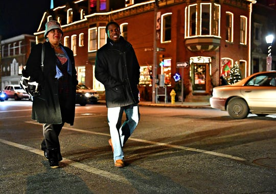 Joanne Wilmore, left, of York City, and Montaski McCoy, of Alabama, cross South Duke Street during First Friday in York City, Friday, Dec. 7, 2018. Dawn J. Sagert photo