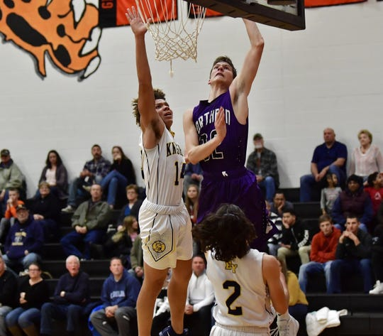 Northern York's Nate Mcgill scores on a layup in front of the defense of Eastern York's Demonte Martin (14) and Bryce Henise on Friday night.