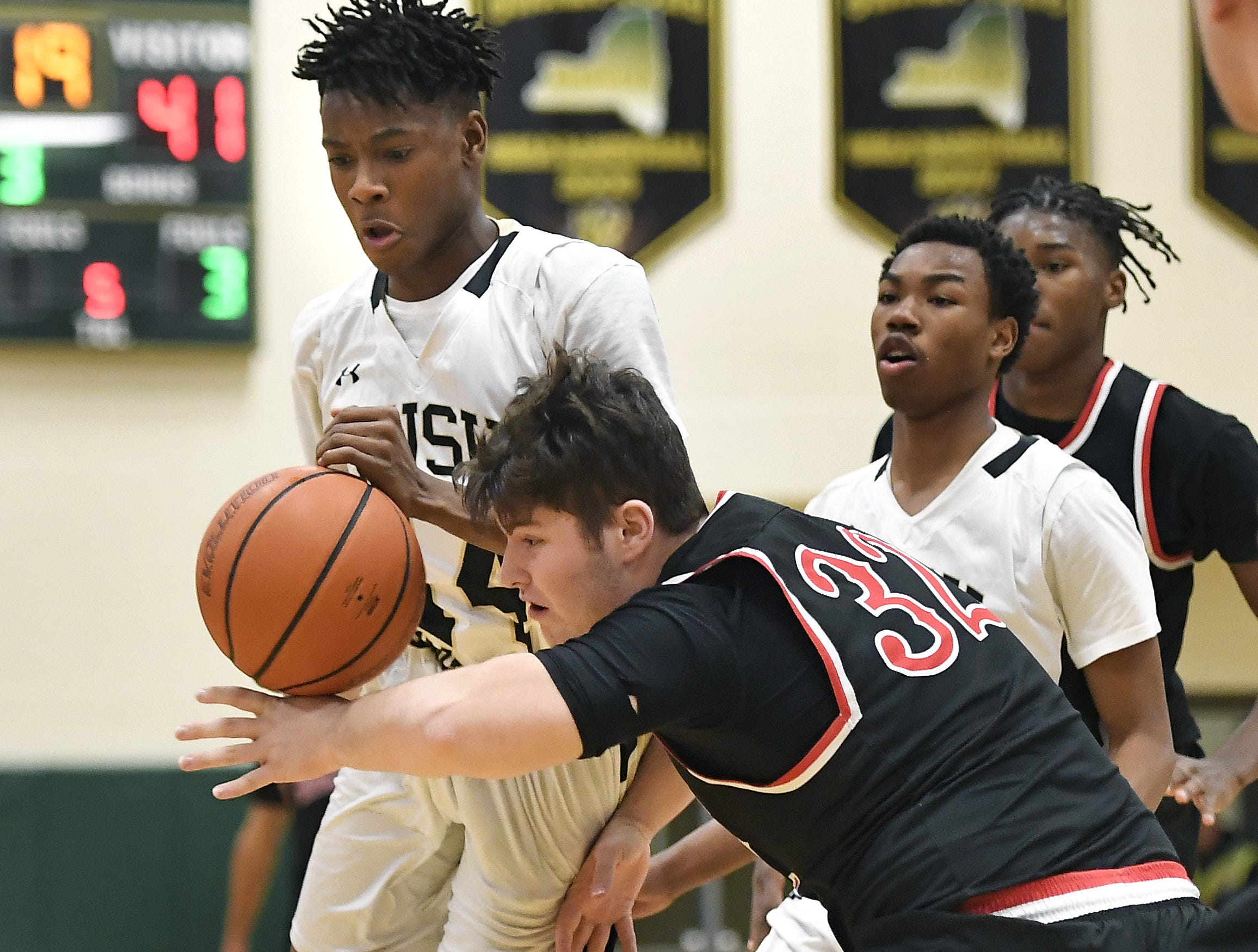 Rush-Henrietta's Eddie Beverly, left, and Hilton's Alex Mistretta reach for a loose ball during a regular season game played at Rush-Henrietta High School, Friday, Dec. 7, 2018. Hilton beat Rush-Henrietta 61-47.
