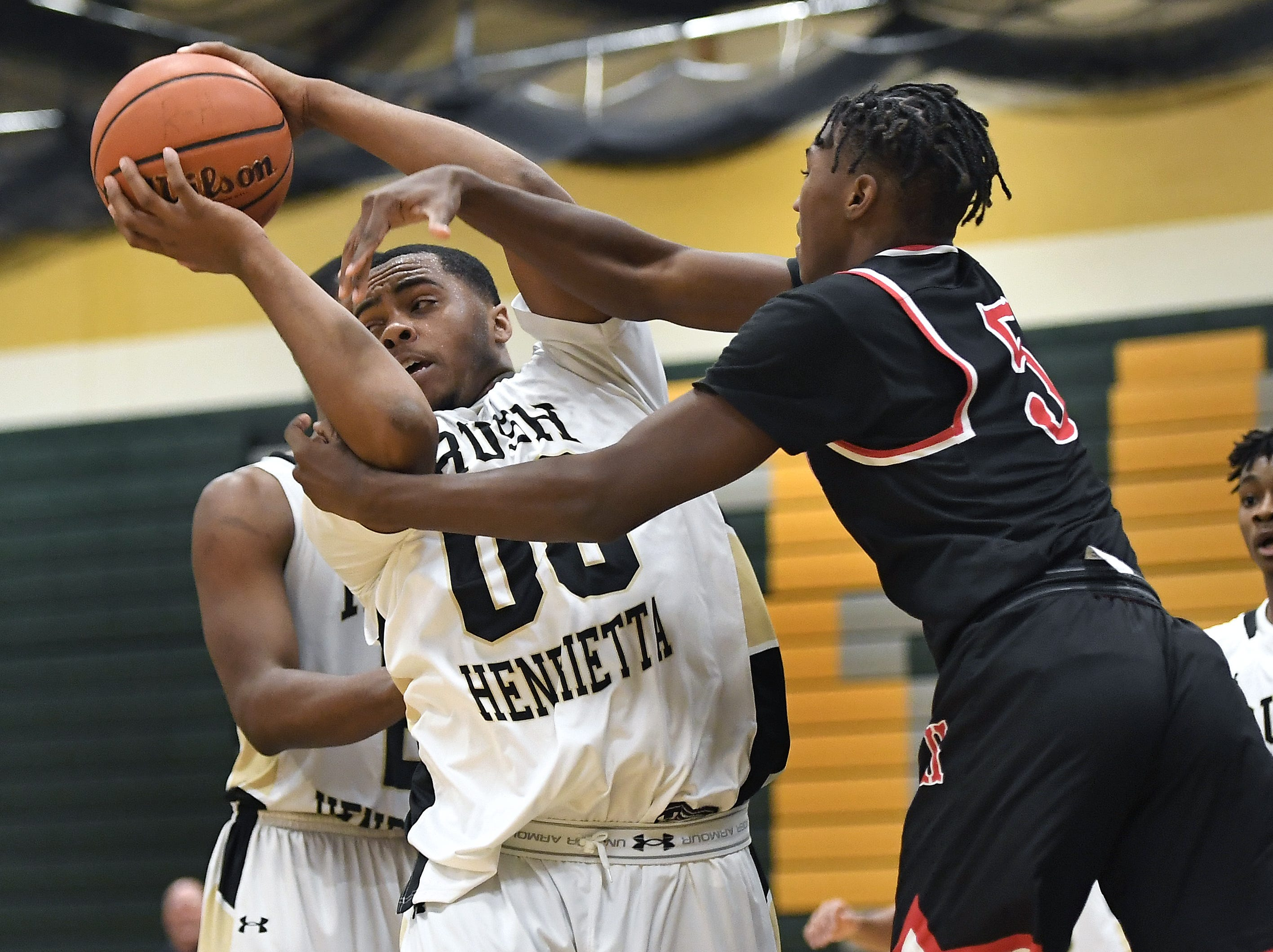 Rush-Henrietta's Nyles Goodwin, left, wins a rebound from Hilton's Najier Daniels during a regular season game played at Rush-Henrietta High School, Friday, Dec. 7, 2018. Hilton beat Rush-Henrietta 61-47.