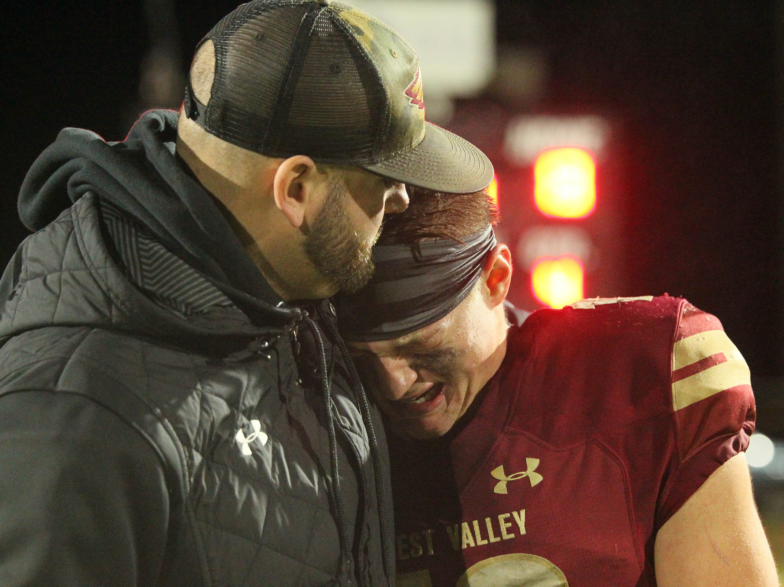 West Valley's Bailey Sulzer embraces with a coach after the game.  Rio Linda beat the Eagles, 21-13, to take the NorCal regional title for Division 5-AA in Red Bluff on Friday, Dec. 7.