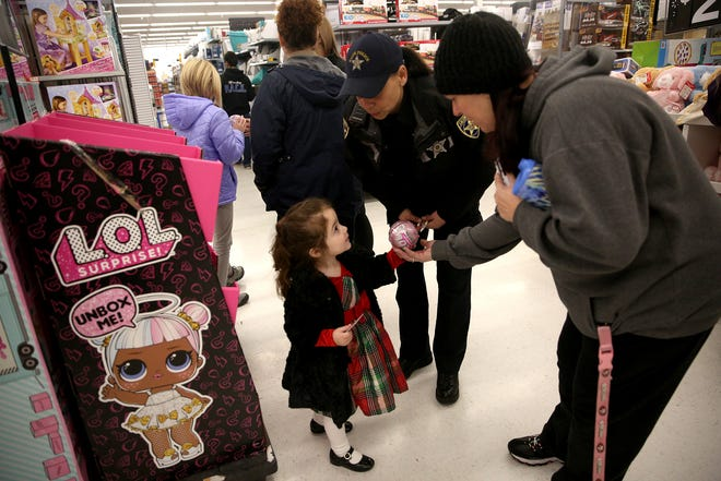 Three-year-old Scarkett Quintilla picks out a toy during the annual Shop with a Cop at the Commercial St SE Walmart in Salem on Saturday, Dec. 8, 2018. More than 600 children participated in this year's event making it the largest yet. Marion County Sheriffs and more than 40 other law enforcement agencies were part of the event.