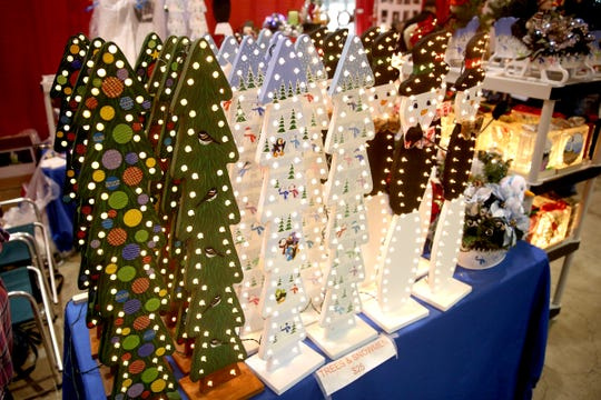 Wooden decorated trees and snowmen are sold at the Salem Holiday Market on Saturday, Dec. 8, 2018.