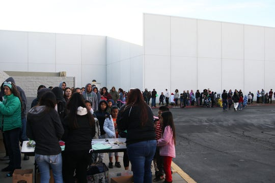 Children stand in line with their families early Saturday before the Children's Shopping Tour began.