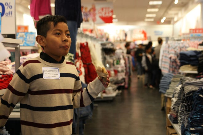 Jose Mendez savored a cookie as he shopped Saturday. He and 249 other children were given $100 by the Salinas Valley Chamber of Commerce Saturday to supplement their winter wardrobes.