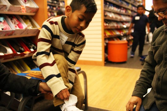 Jose Mendez tries on a pair of sneakers on the annual Children's Shopping Tour.