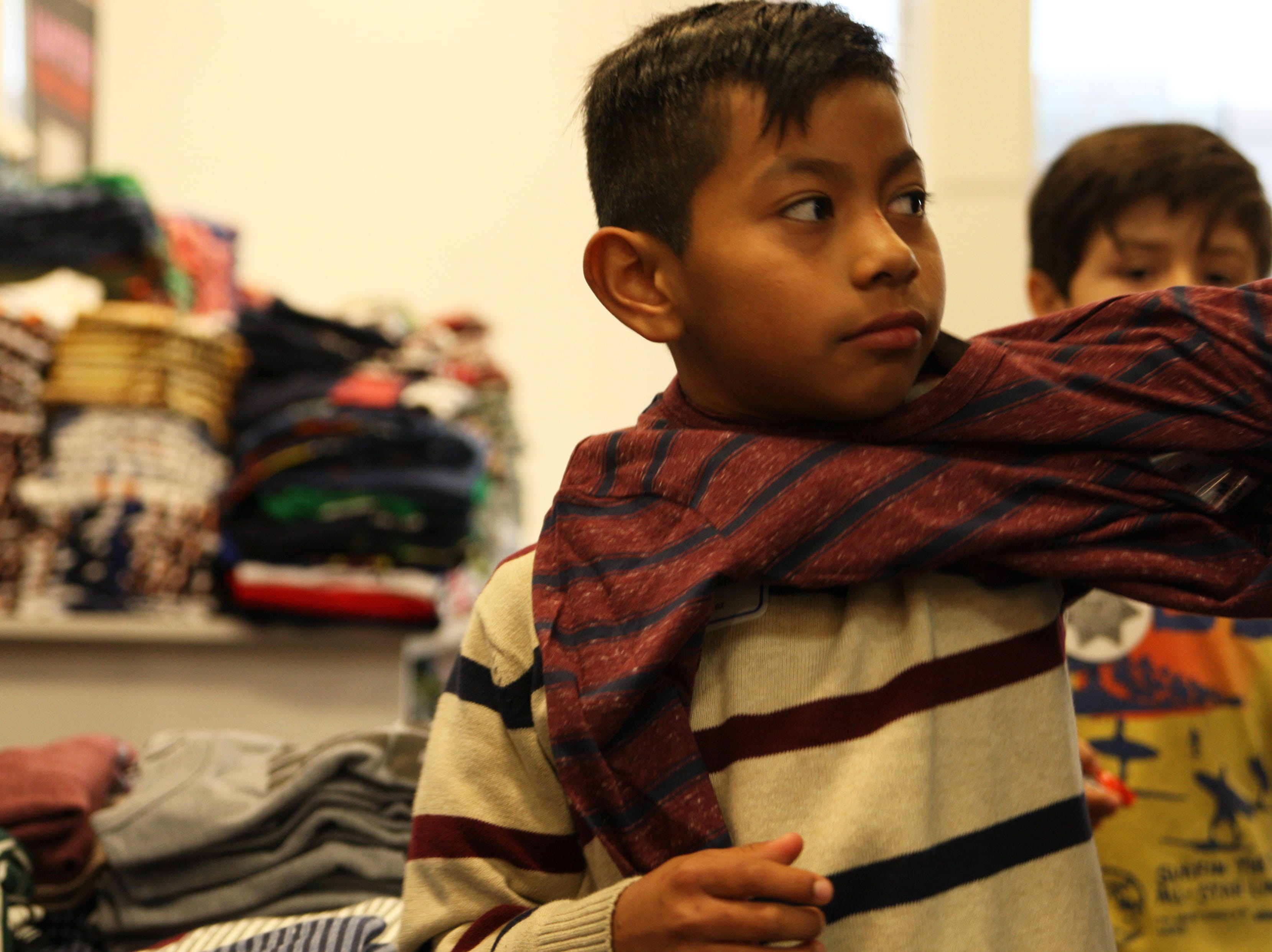 Jose Mendez tries on a long-sleeved shirt Saturday at the Children's Shopping Tour. Jose was given $100 by the Salinas Valley Chamber of Commerce to supplement a winter wardrobe.
