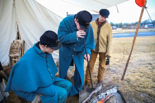 Winter Rendezvous participants keep a fire going Friday, Dec. 7, 2018, during Christmas at Old Fort Concho.