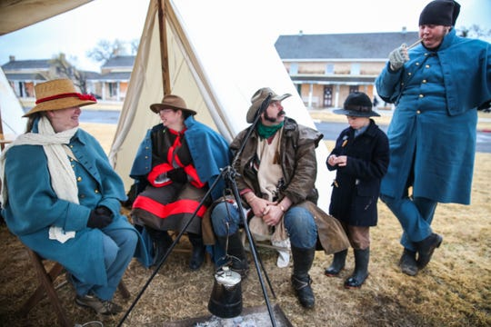 Winter Rendezvous participants sit by a fire Friday, Dec. 7, 2018, during Christmas at Old Fort Concho.