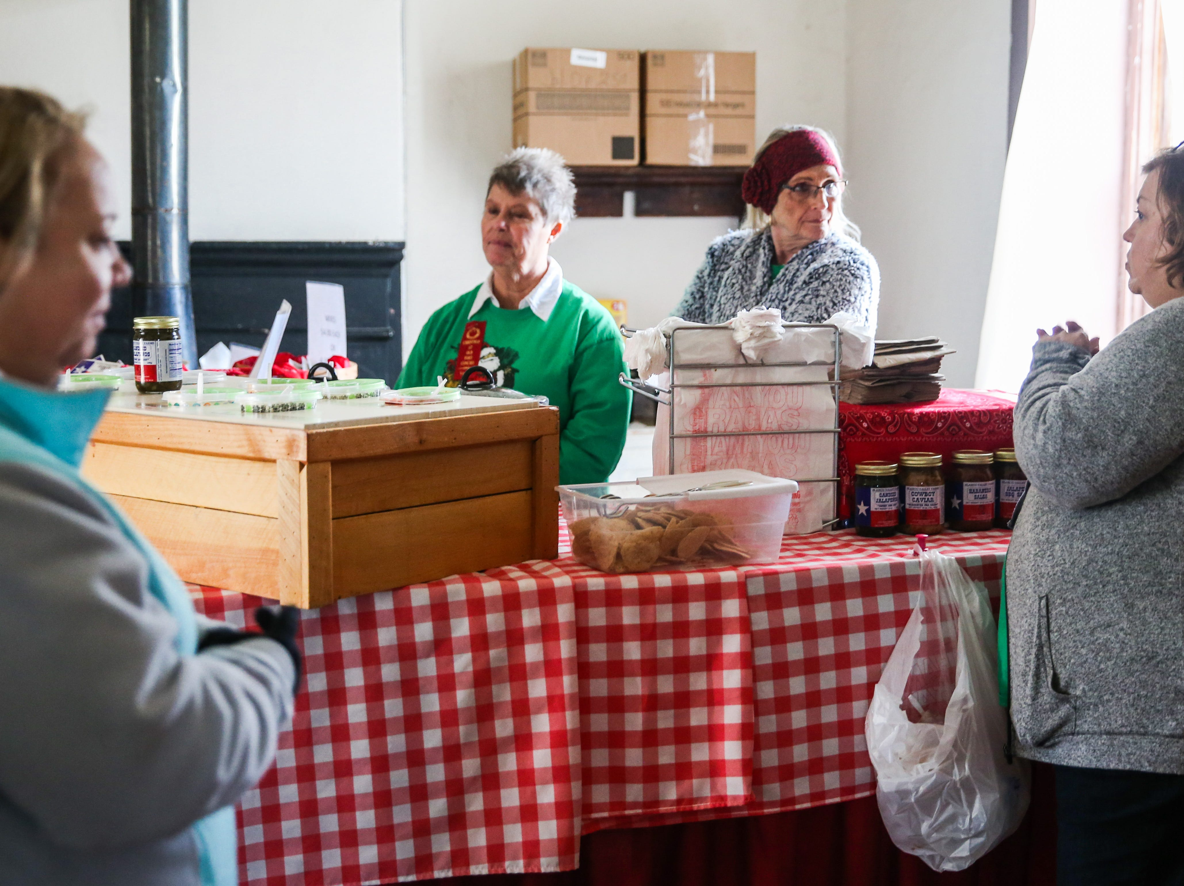 Shoppers chat with merchants in a fort building Friday, Dec. 7, 2018, during Christmas at Old Fort Concho.