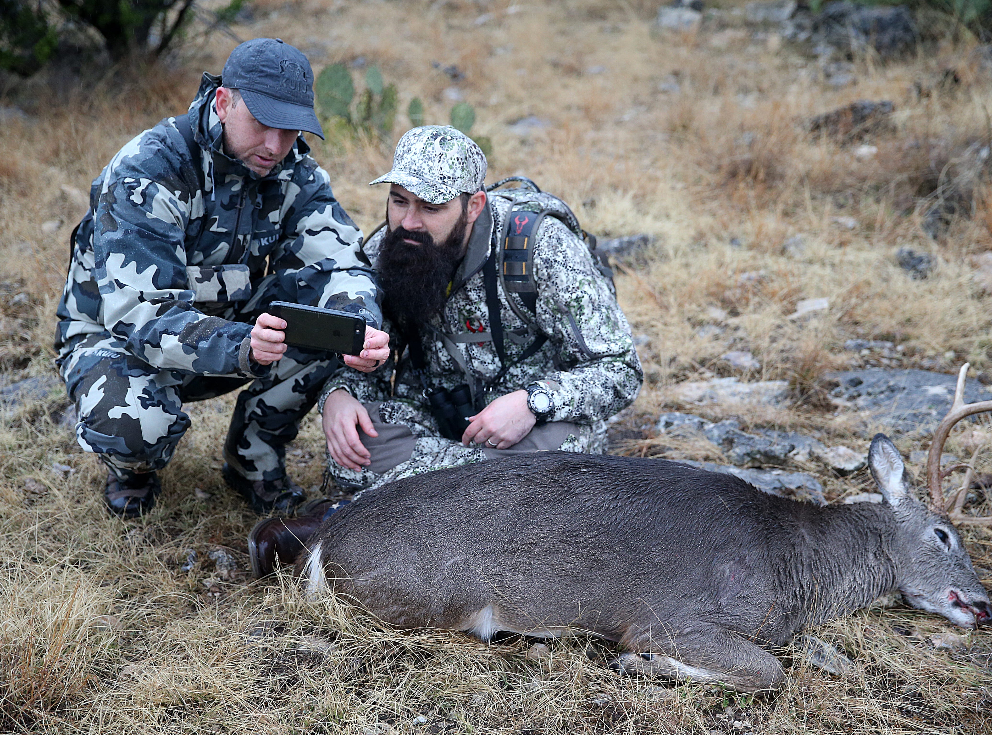 Ryan Dupriest (left) shows Joseph Lewis photos of himself posing with his deer Friday, Dec. 7, 2018 during the annual deer hunt in Christoval sponsored by San Angelo Support for Veterans and Lone Star Warriors Outdoors.