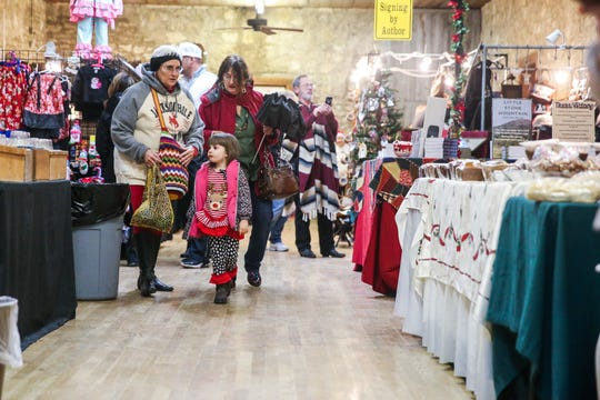 Shoppers walk by merchant booths in a fort building Friday, Dec. 7, 2018, during Christmas at Old Fort Concho.