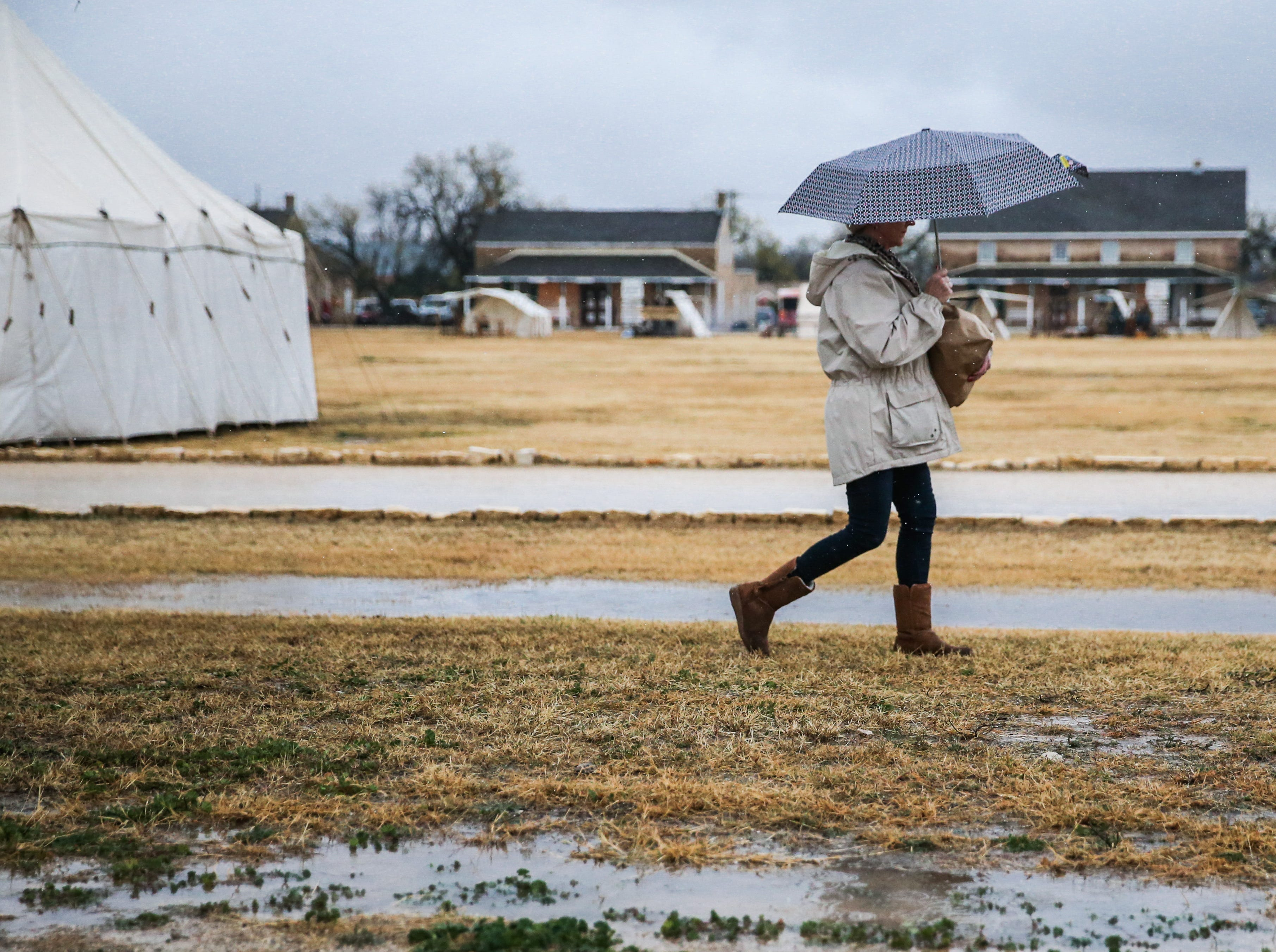 A visitor walks in the wet grass between buildings Friday, Dec. 7, 2018, during Christmas at Old Fort Concho.