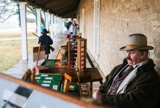 Jerry Eastman aka William Bat Masterson sits on the porch of a building as visitors and reenactors walk by Friday, Dec. 7, 2018, during Christmas at Old Fort Concho.
