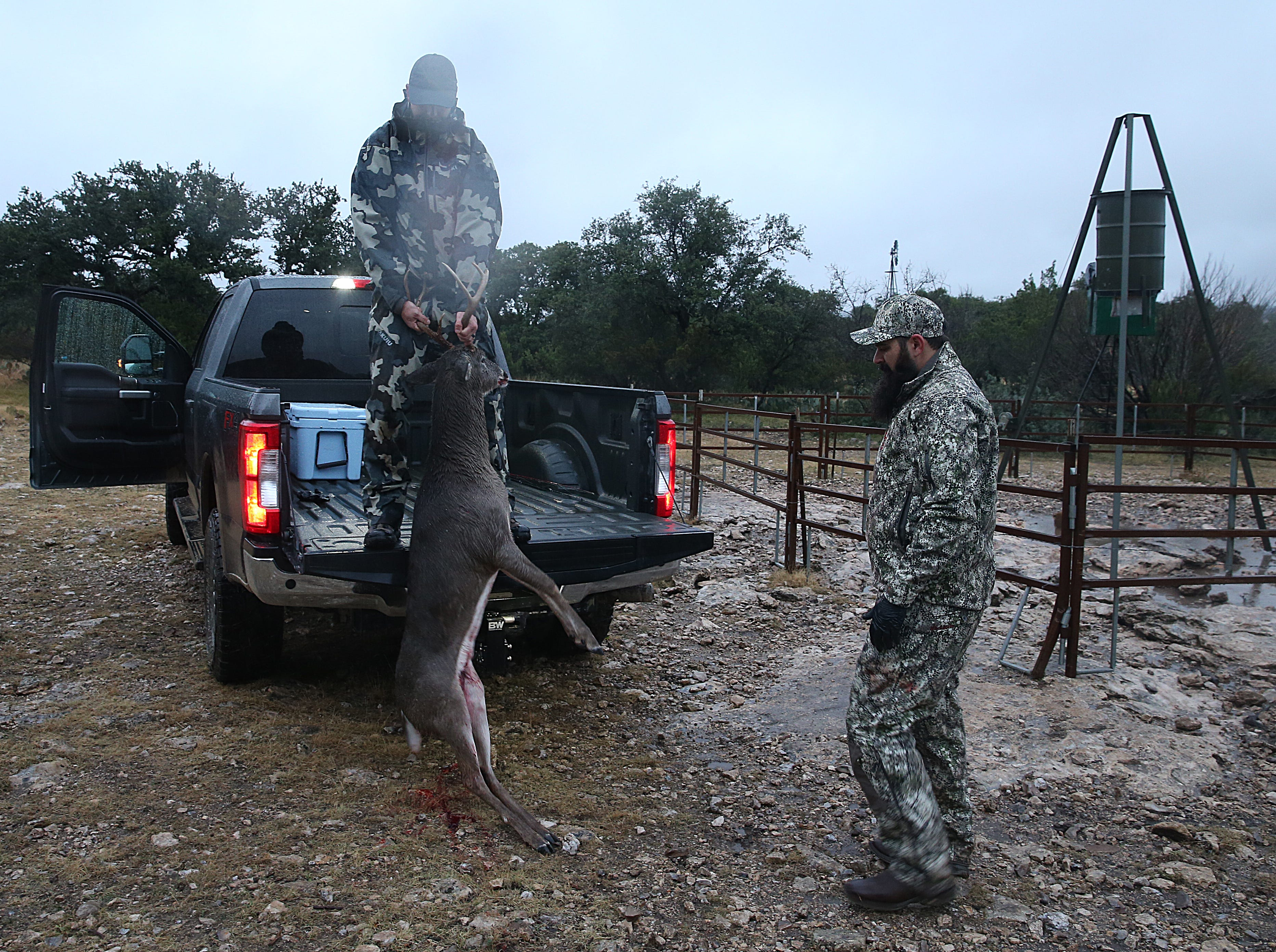 Hunters Ryan Dupriest (left) and Joseph Lewis load a deer onto their truck Friday, Dec. 7, 2018 during the annual deer hunt in Christoval sponsored by San Angelo Support for Veterans and Lone Star Warriors Outdoors.