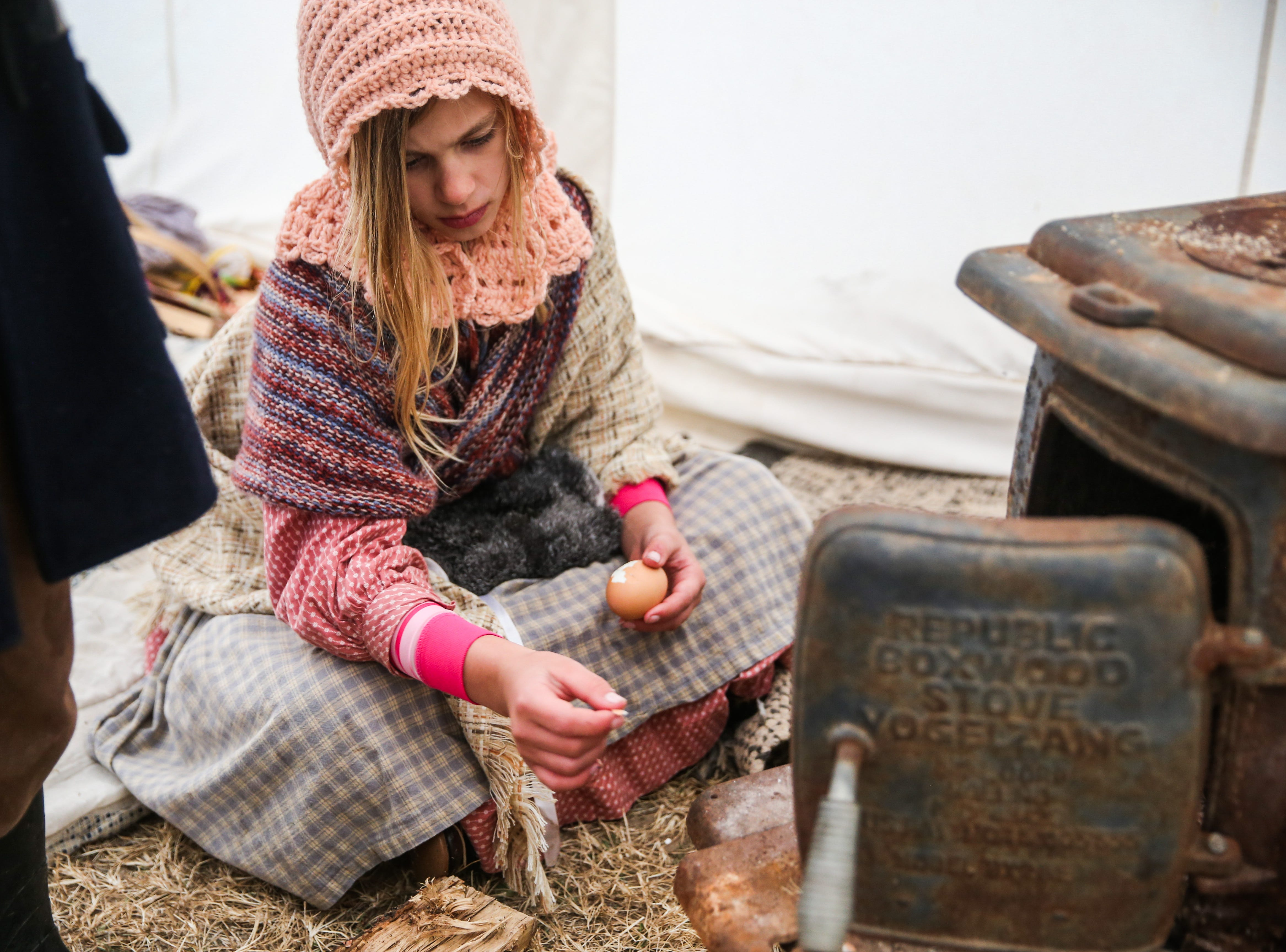 Pecos Hopkins, 9, piles an egg for a snack at camp Friday, Dec. 7, 2018, during Christmas at Old Fort Concho.