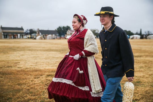Reenactors Alana Franklin, 16, and Dustin Schneider walk across the field Friday, Dec. 7, 2018, during Christmas at Old Fort Concho.