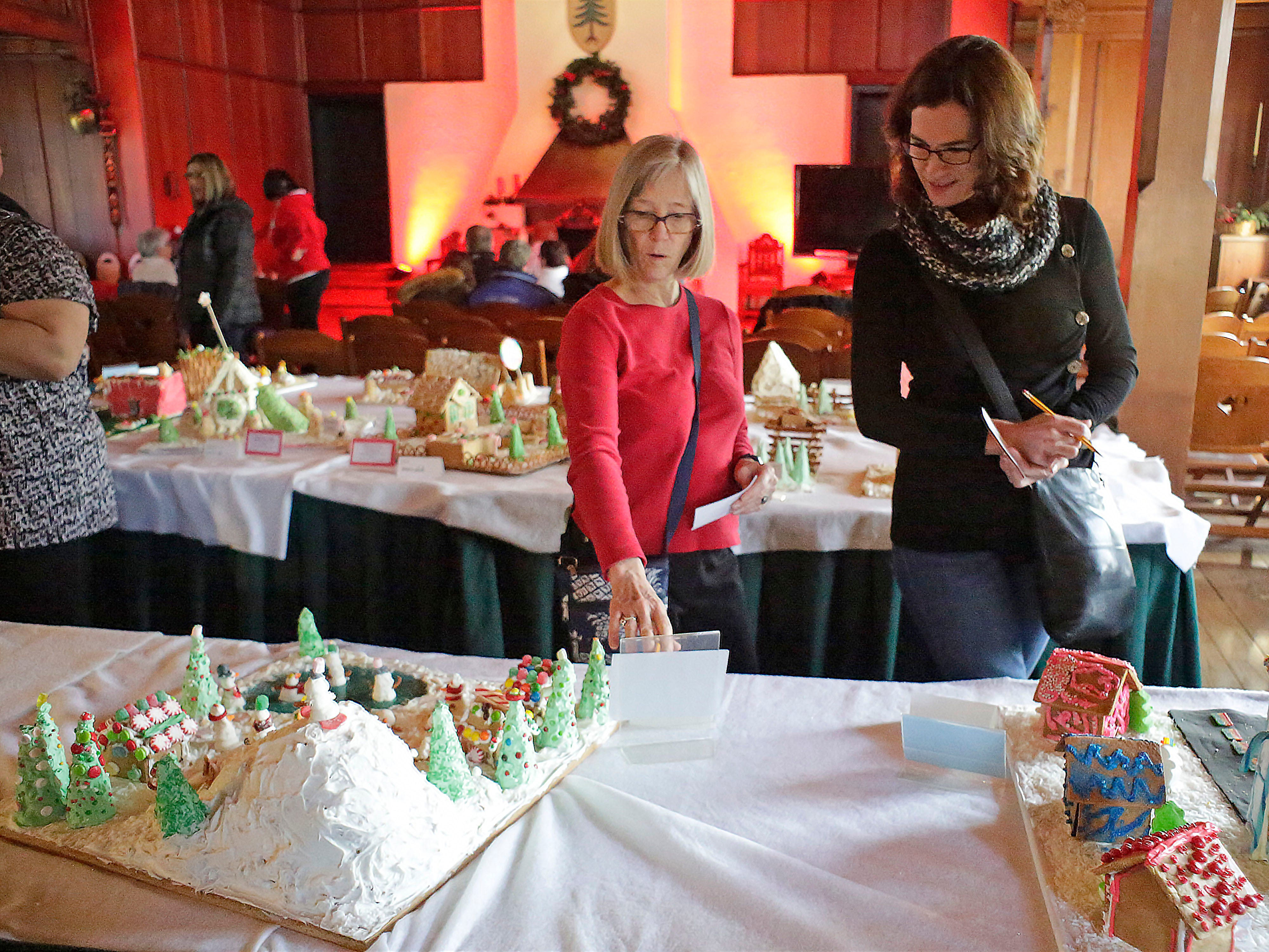 Sally Isely, left, and Stephani Newby, both  of Plymouth, Wis., look over gingerbreads during the annual Waelderhaus Gingerbread Festival, Saturday, December 8, 2018, in Kohler, Wis.