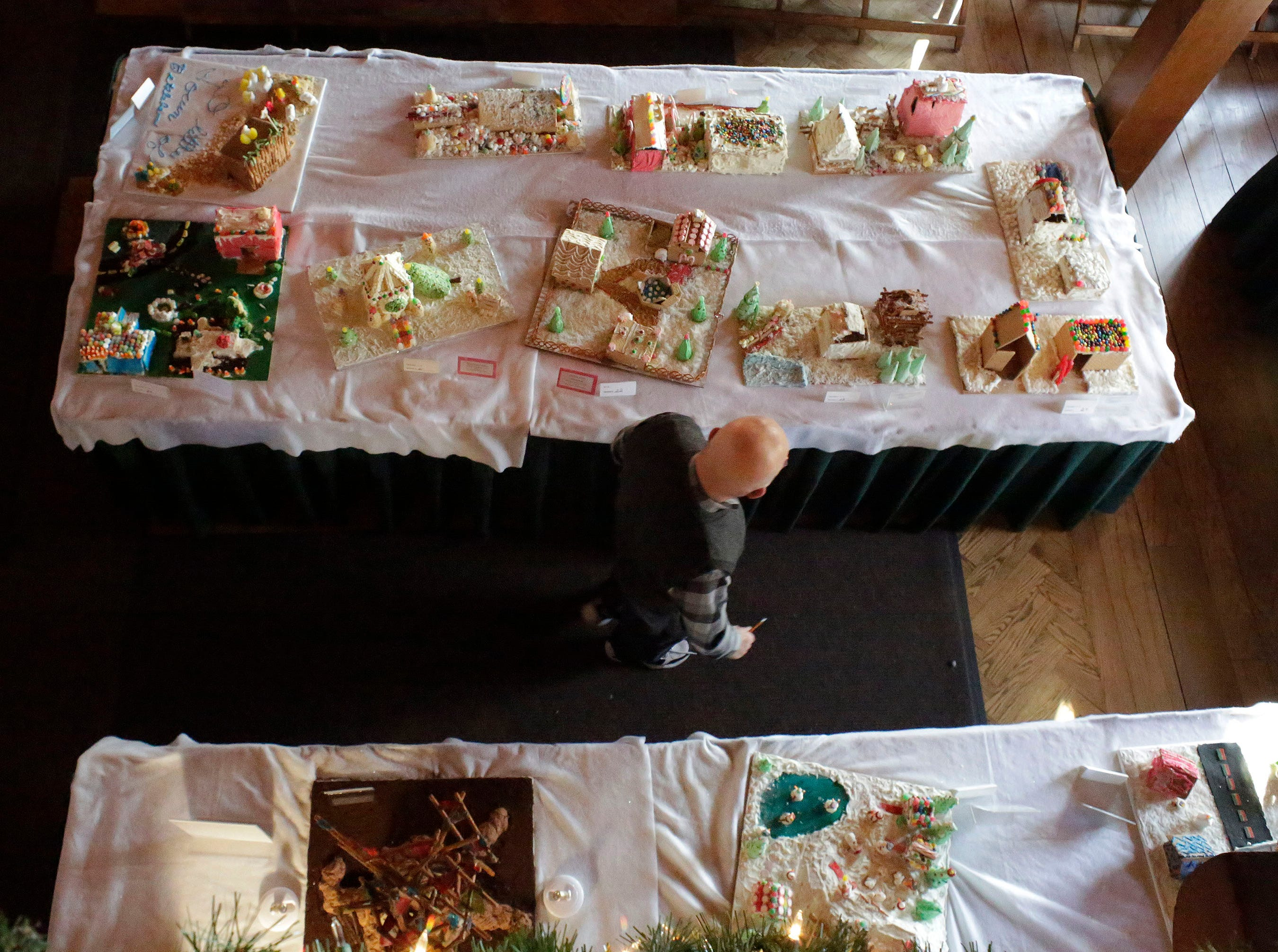 A man inspects gingerbreads at the annual Waelderhaus Gingerbread Festival, Saturday, December 8, 2018, in Kohler, Wis.
