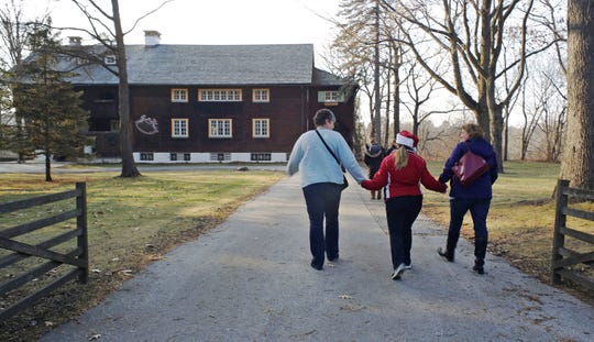 A trio walks hand in hand to the annual Waelderhaus Gingerbread Festival, Saturday, December 8, 2018, in Kohler, Wis.