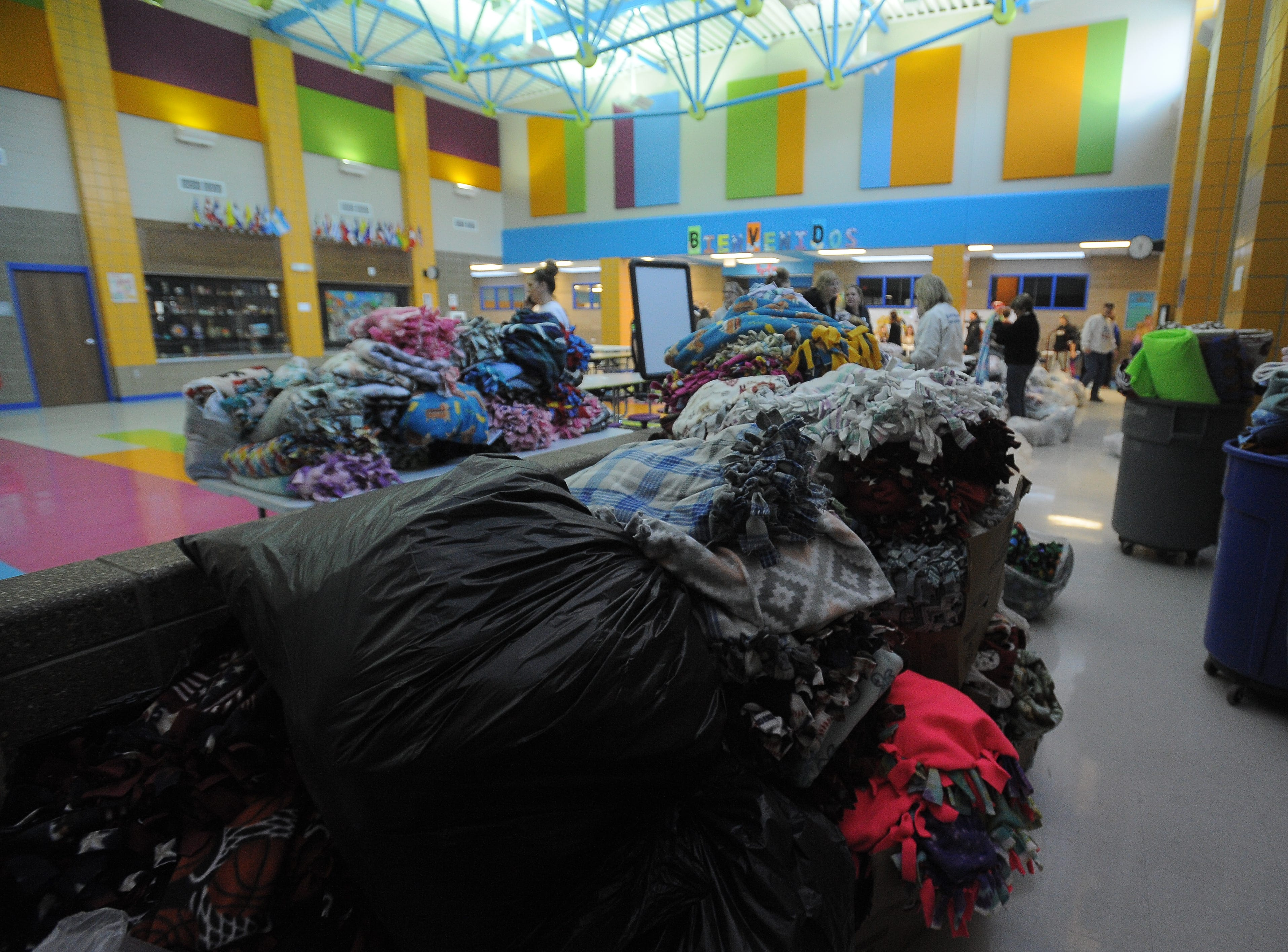 Piles of made blankets wait to be put into boxes to be delivered to Sioux Falls schools. The blankets were made through Project Warm-Up.