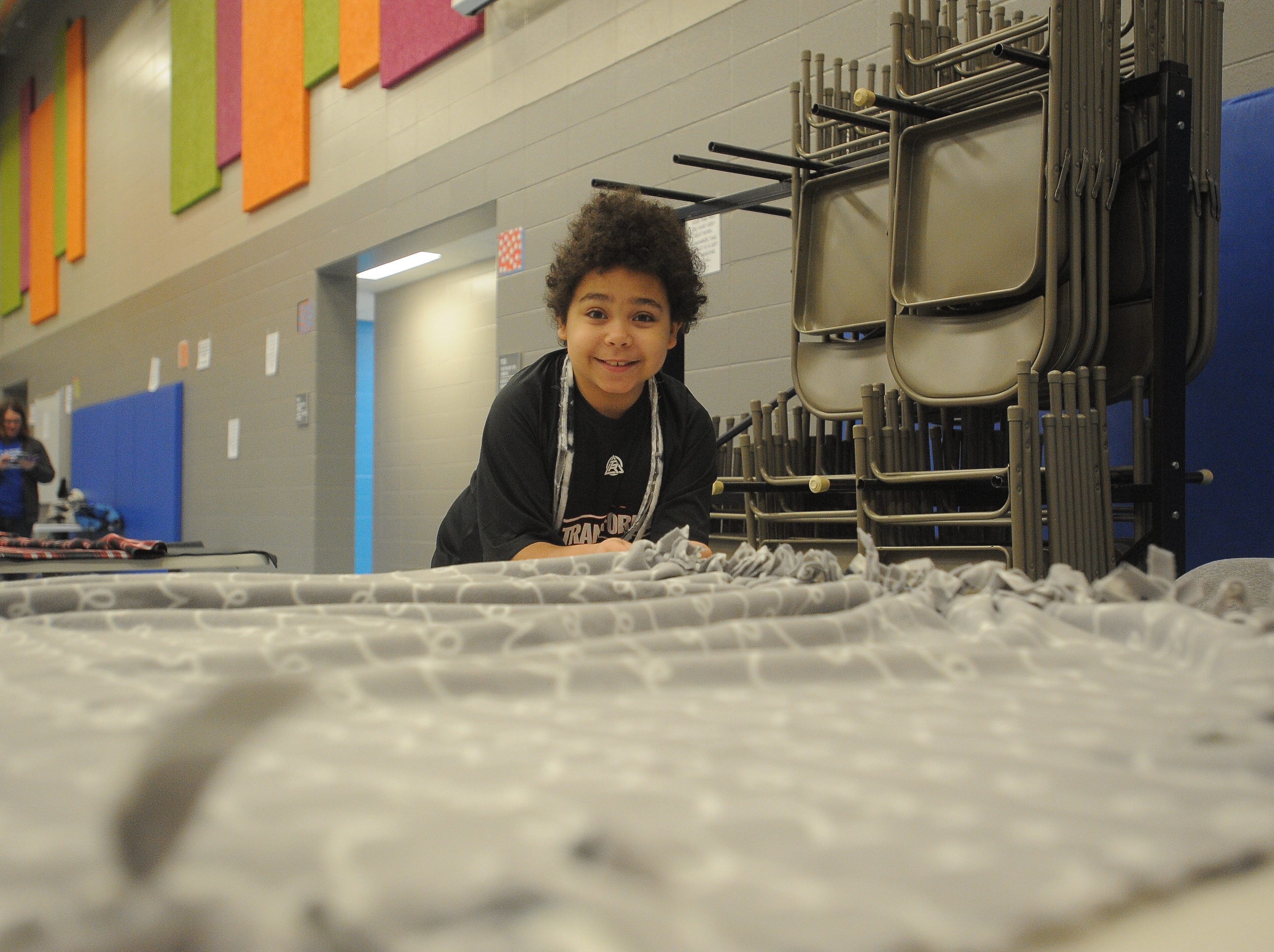 Jeremiah, 10, a fourth-grader at Sonia Sotomayor Elementary, makes a tie blanket for Project Warm-Up Saturday, Dec. 8, 2018. Hundreds of volunteers come to make blankets that are distributed to area children in need.