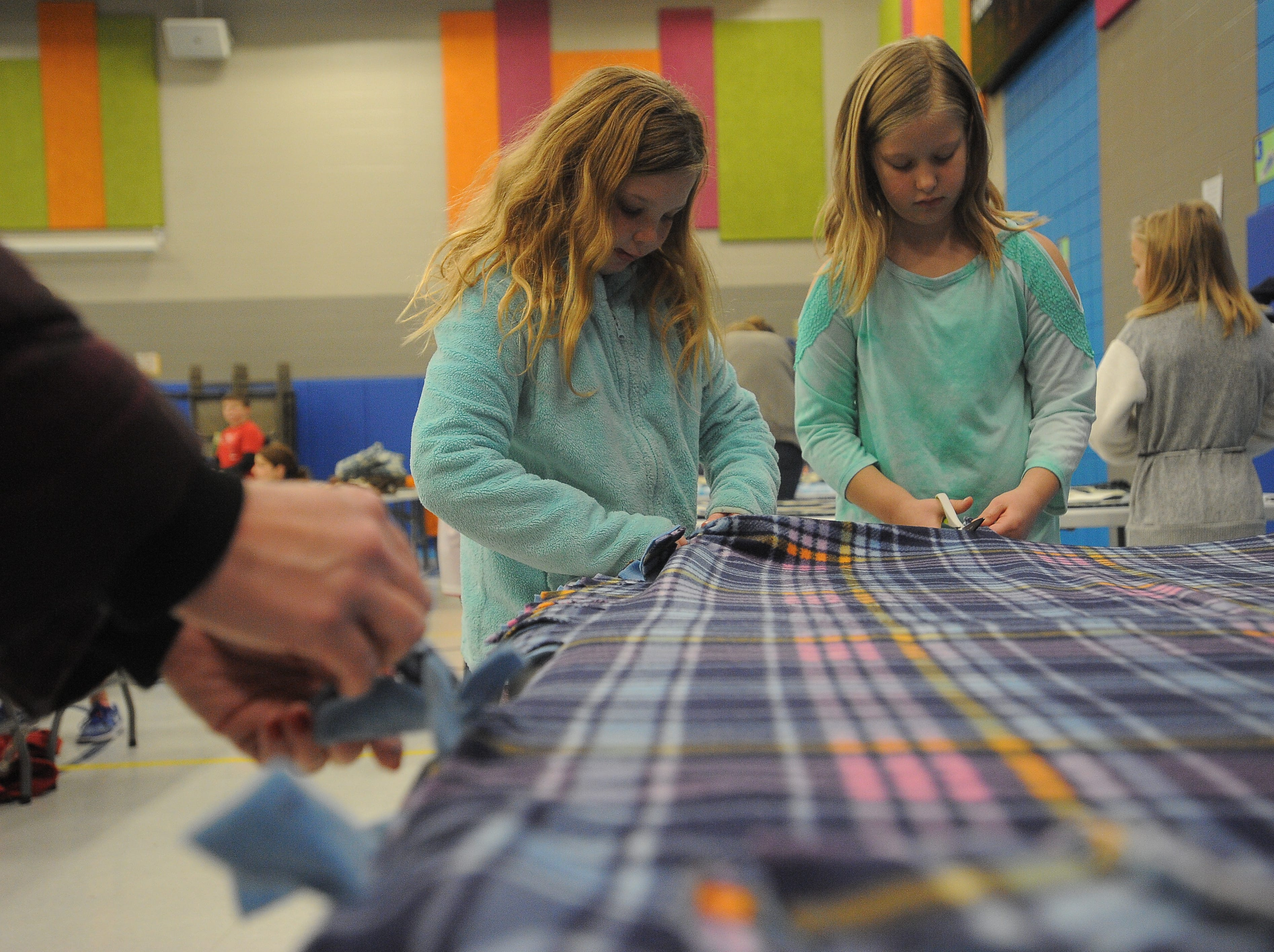 Mya, 8, and Addison, 9, make tie blankets Saturday, Dec. 8, 2018, as part of Project Warm-Up. In its 13th year, the project has delivered more than 20,000 blankets to children in need in and around Sioux Falls.