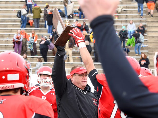 Riverheads' head coach Robert Casto holds up the championship trophy after they win the VHSL Class 1 championship game in Salem on Saturday, Dec. 8, 2018.
