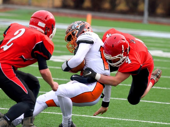 Riverheads' Blake Smith (#4) grabs onto a Chilhowie ballcarrier to make the stop as teammate Devin Morris (#2) looks to get in on the tackle during the VHSL Class 1 championship game in Salem on Saturday, Dec. 8, 2018.