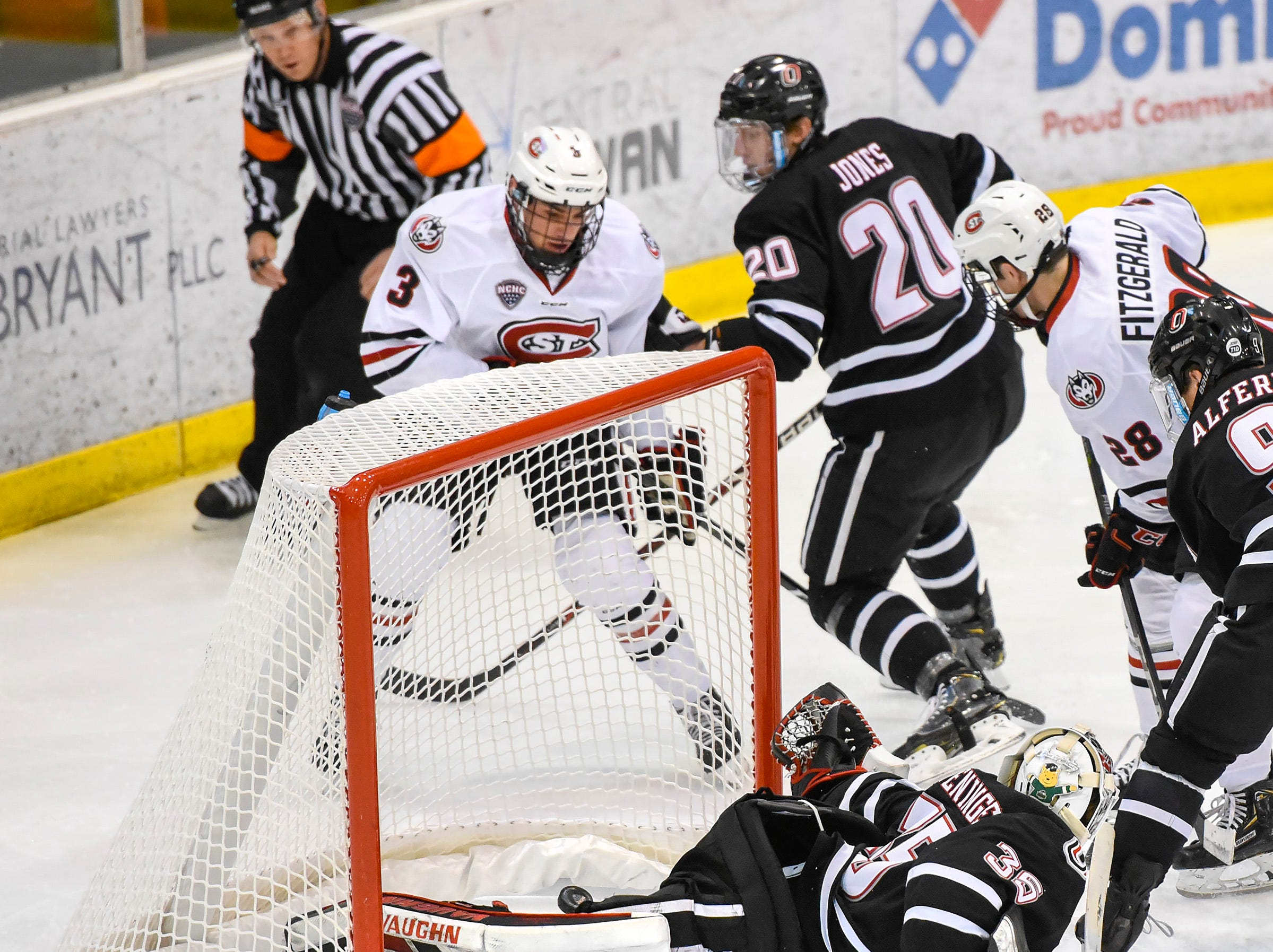 St. Cloud State's Jack Poehling, 3, slips the puck behind Nebraska-Omaha's goalie Evan Weninger to score during the first period Friday, Dec. 7, at the Herb Brooks National Hockey Center.