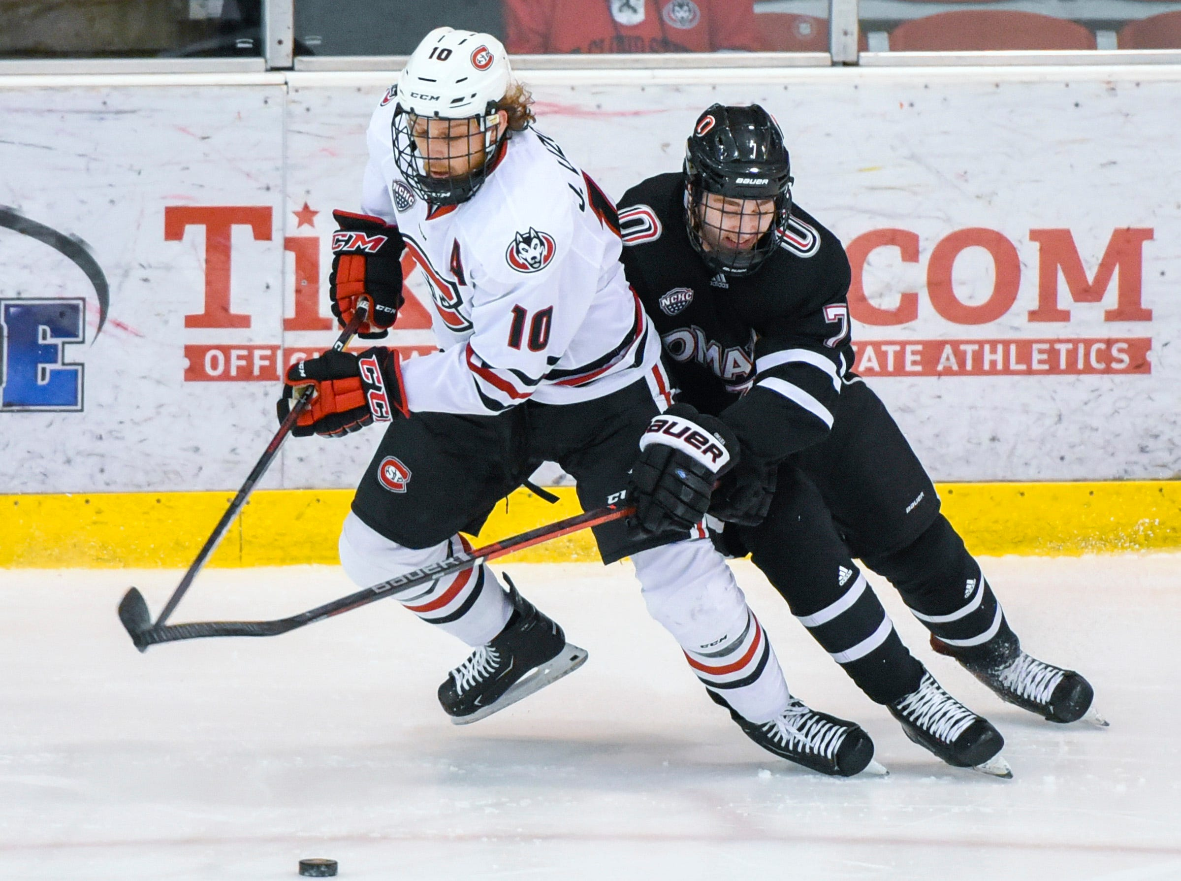 St. Cloud State's Jon Lizotte and Nebraska-Omaha's Nate Knoepke battle for a loose puck during the first period Friday, Dec. 7, at the Herb Brooks National Hockey Center.