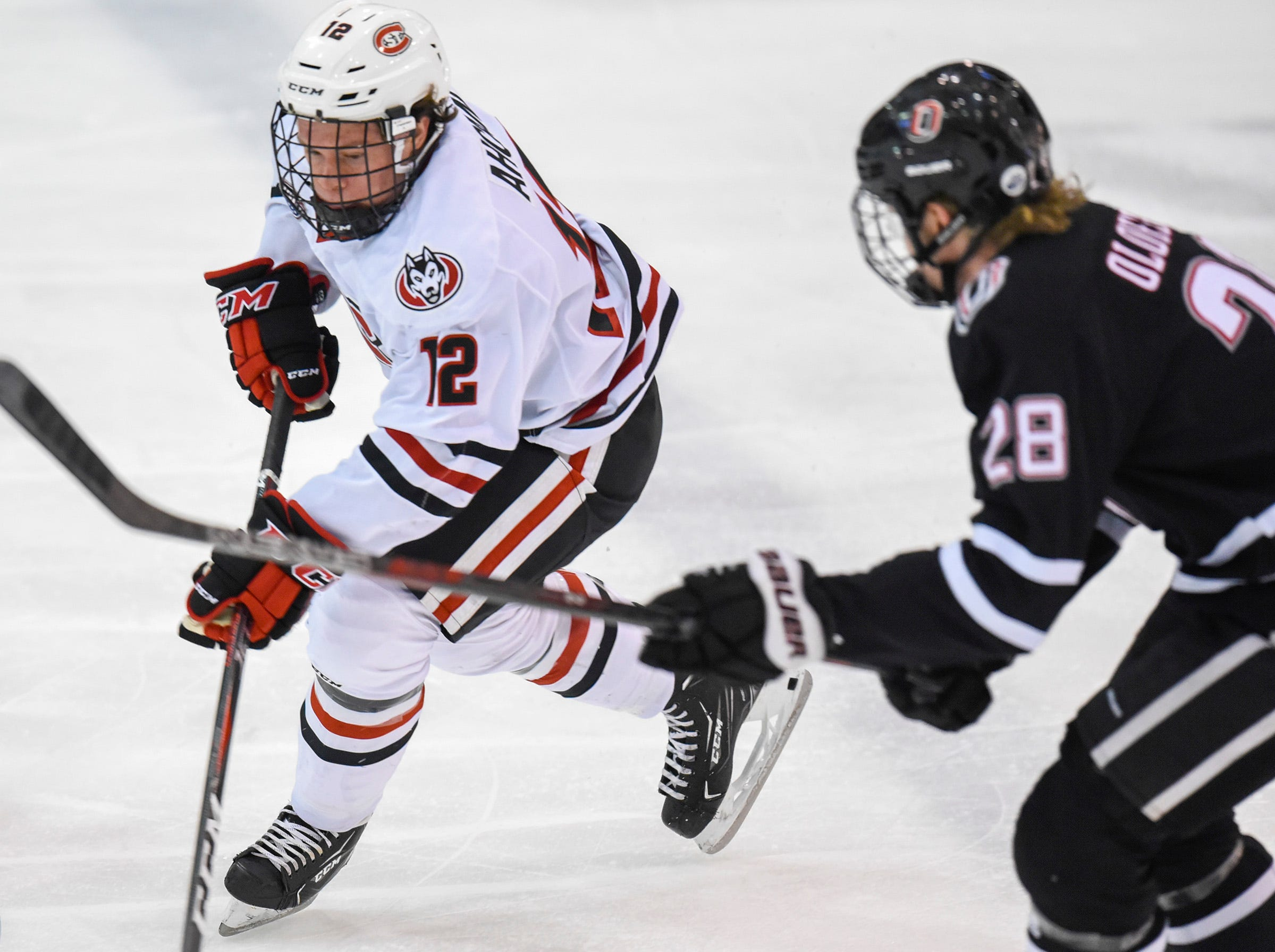 St. Cloud State's Jack Ahcan takes the puck past Nebraska-Omaha's Fredrik Olofsson during the first period Friday, Dec. 7, at the Herb Brooks National Hockey Center.