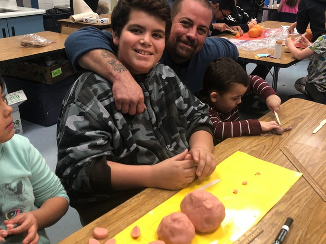 Ben Ramirez and son Ben Ramirez Jr. participate in the Planet Play-Doh station at the J.L. Bowler Elementary School family science night.