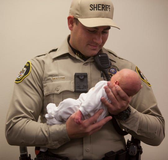 Washington County Sheriff's Deputy Erick Baron holds Bella Kaye, daughter of Nicole Bishop and Michael Brown, in Hurricane on Dec. 8, 2018. Baron helped Bishop deliver the little girl on the side of state Route 59.