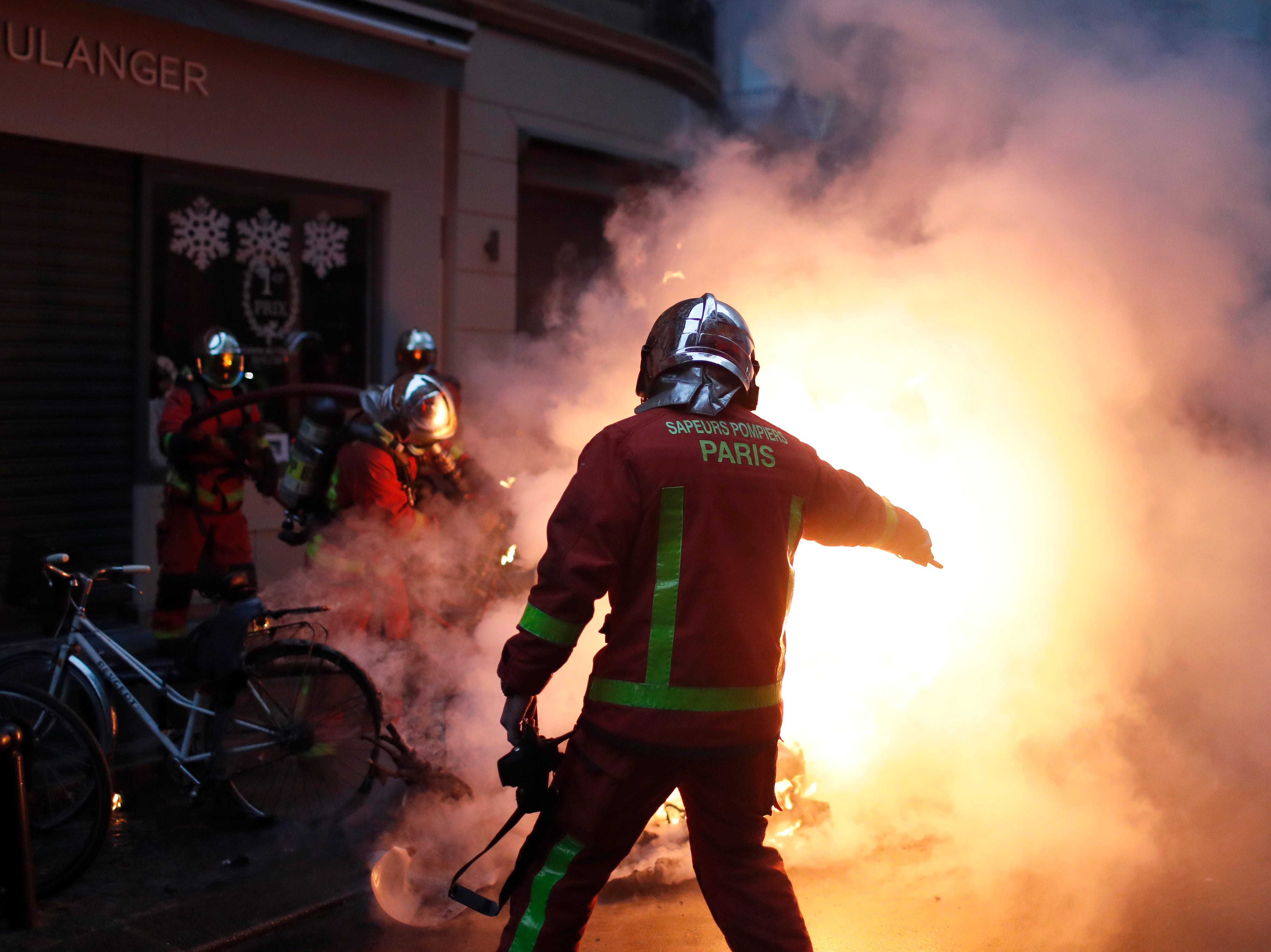 Firefighters try to extinguished a car set on fire by demonstrators during clashes with riot police, in Paris, France, Saturday, Dec. 8, 2018. Crowds of protesters angry at President Emmanuel Macron and France's high taxes tried to converge on the presidential palace Saturday, some scuffling with police firing tear gas, amid exceptional security measures aimed at preventing a repeat of last week's rioting.
