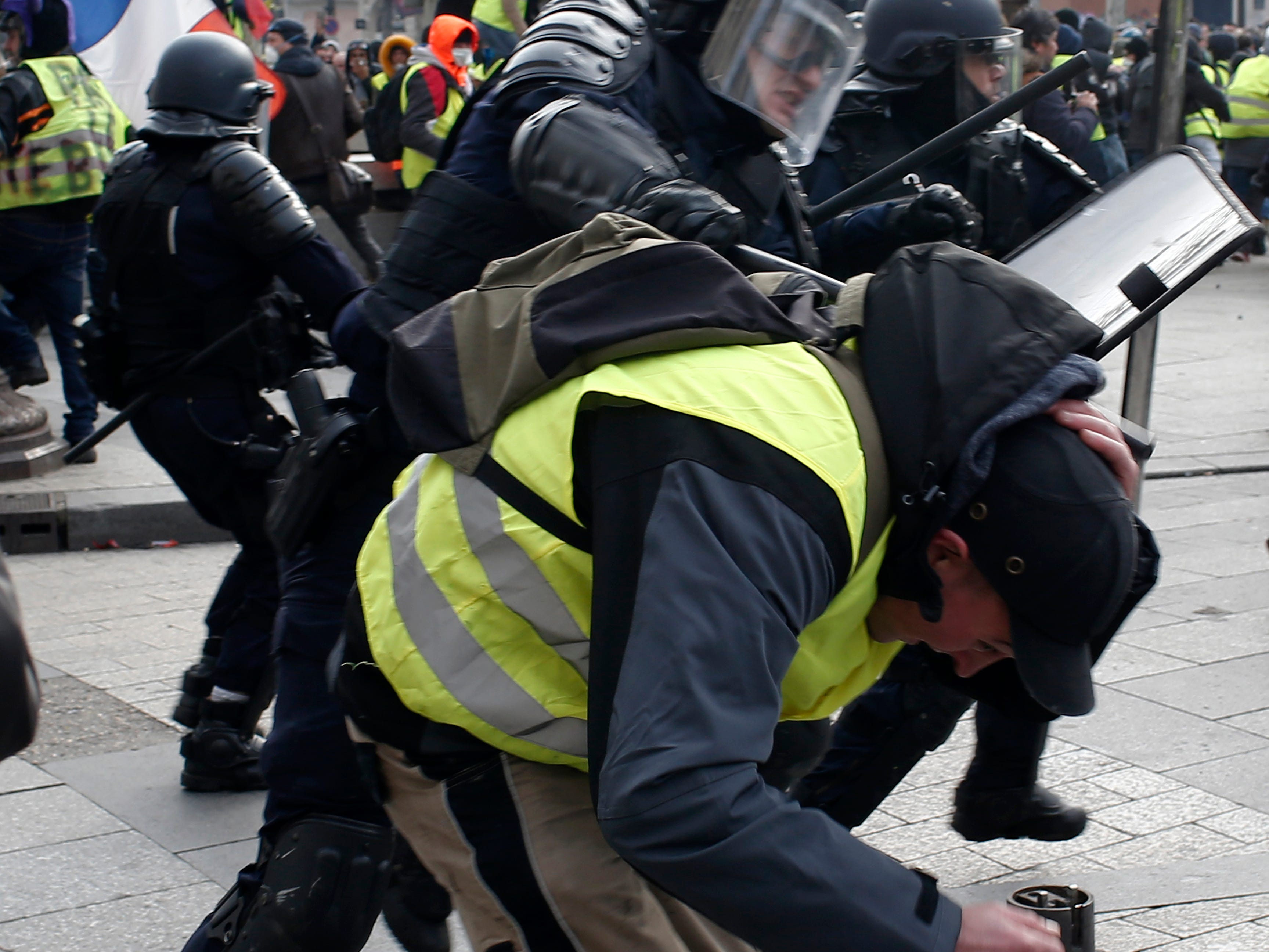 A riot police officer beats a demonstrator on the Champs-Elysees avenue Saturday, Dec. 8, 2018, in Paris. Crowds of yellow-vested protesters angry at President Emmanuel Macron and France's high taxes tried to converge on the presidential palace Saturday, some scuffling with police firing tear gas, amid exceptional security measures aimed at preventing a repeat of last week's rioting.
