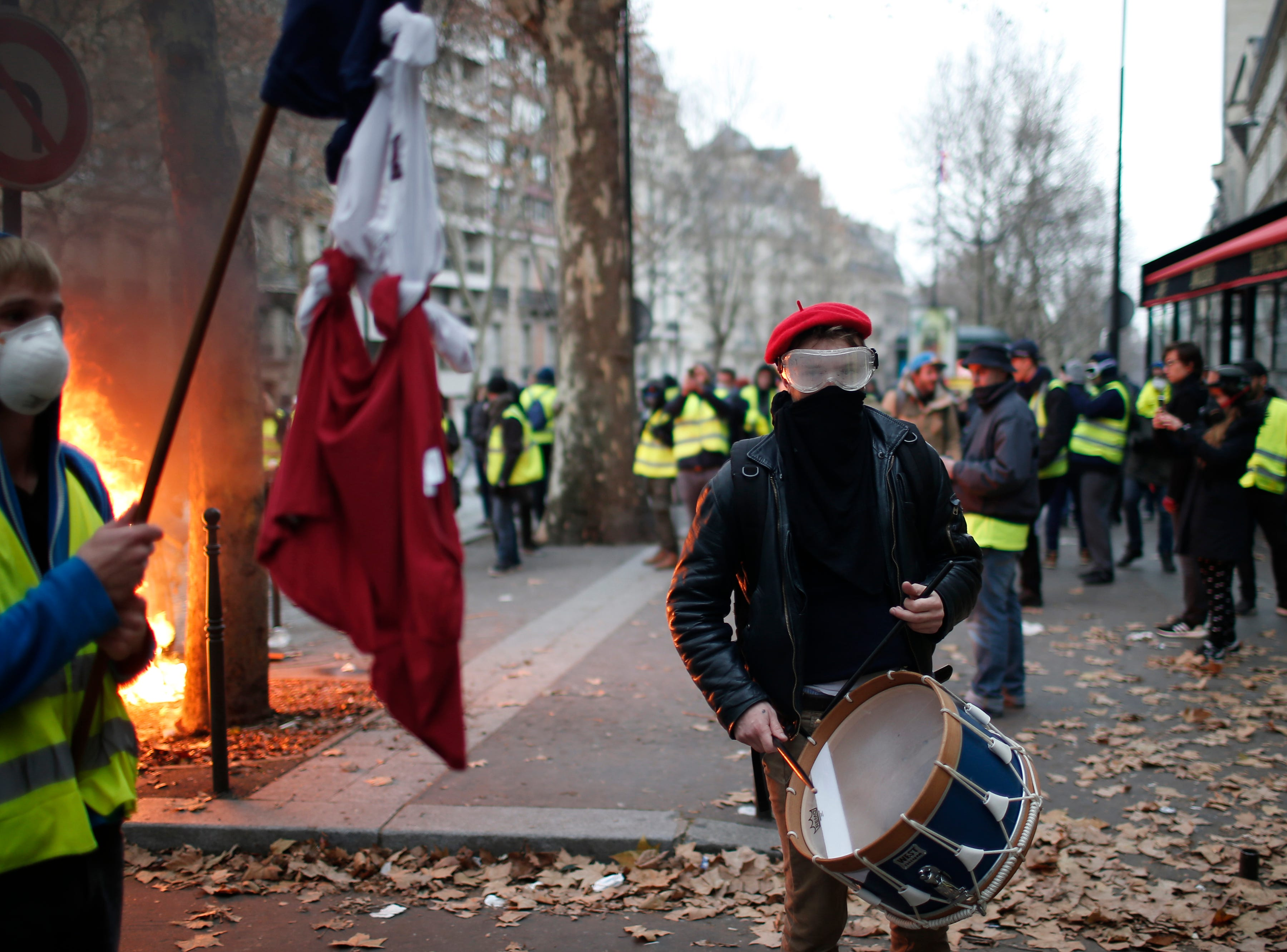 A demonstrator plays a drum Saturday, Dec. 8, 2018, in Paris. Crowds of yellow-vested protesters angry at President Emmanuel Macron and France's high taxes tried to converge on the presidential palace Saturday, some scuffling with police firing tear gas, amid exceptional security measures aimed at preventing a repeat of last week's rioting.
