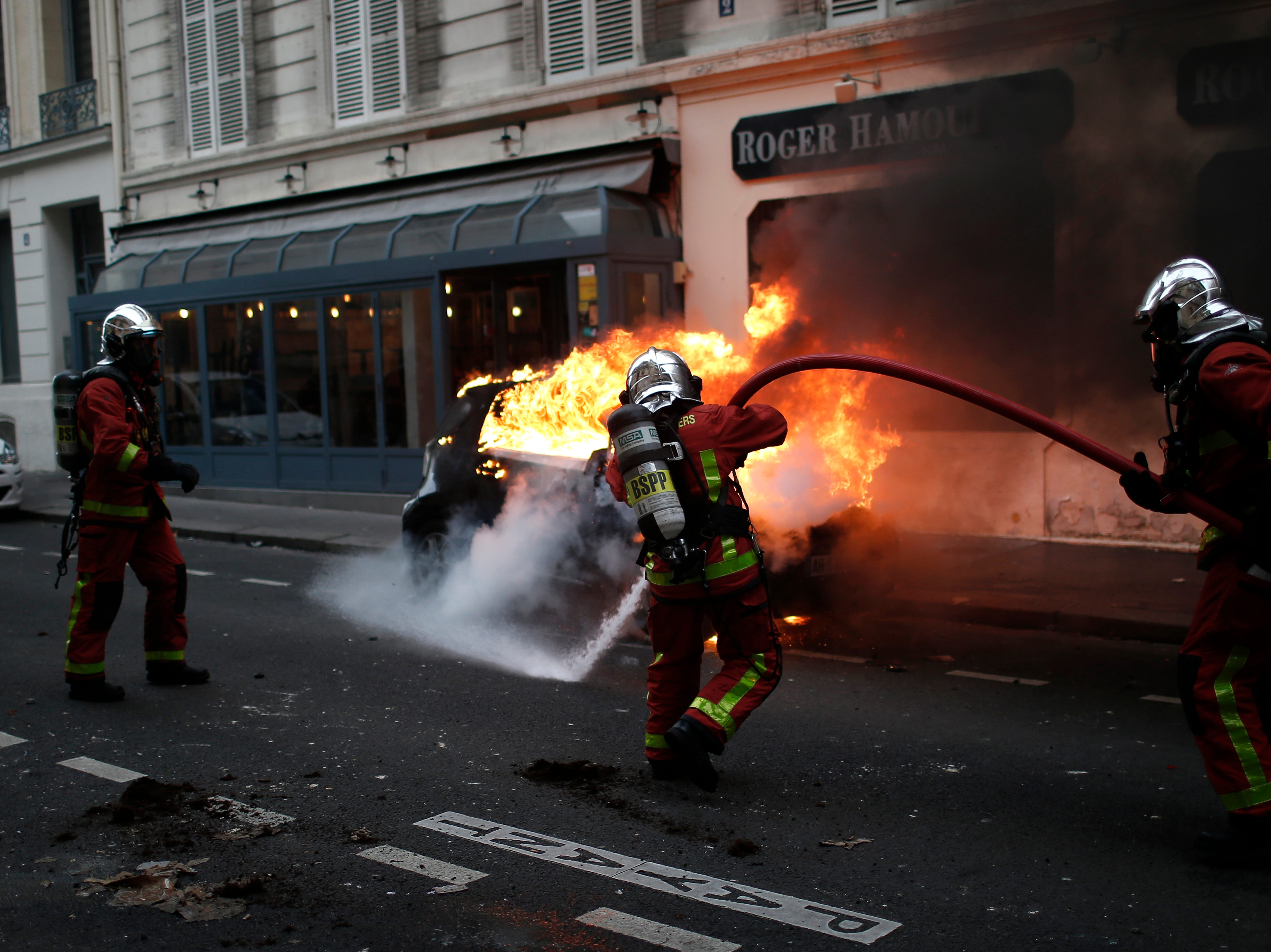 Firefighters put off a fire after clashes Saturday, Dec. 8, 2018, in Paris. French riot police fired tear gas and water cannon in Paris on Saturday, trying to stop thousands of yellow-vested protesters from converging on the presidential palace to express their anger at high taxes and French President Emmanuel Macron.
