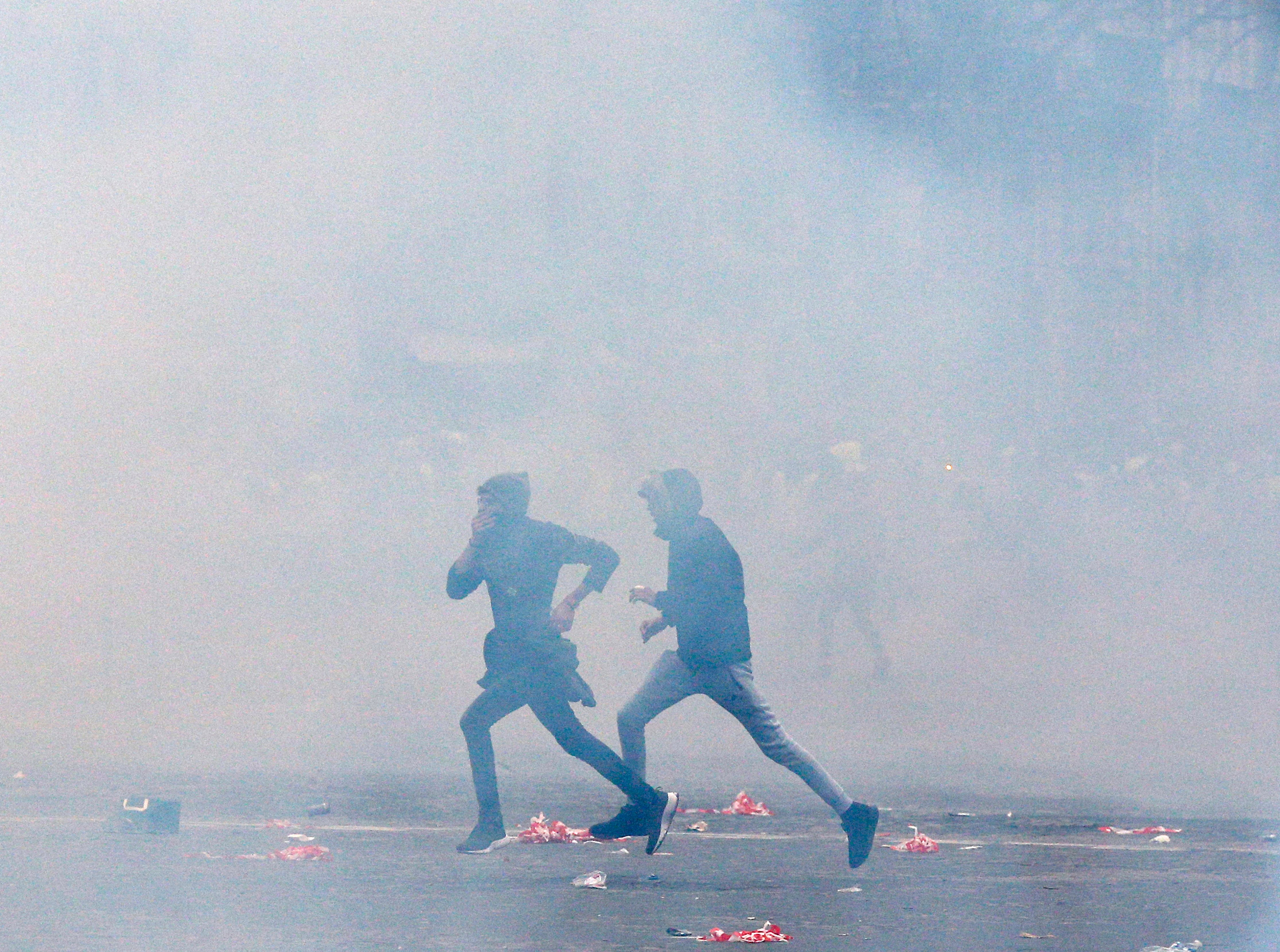 Demonstrators run away from tear gas fired by riot police during clashes in Paris, France, Saturday, Dec. 8, 2018. Crowds of protesters angry at President Emmanuel Macron and France's high taxes tried to converge on the presidential palace Saturday, some scuffling with police firing tear gas, amid exceptional security measures aimed at preventing a repeat of last week's rioting.