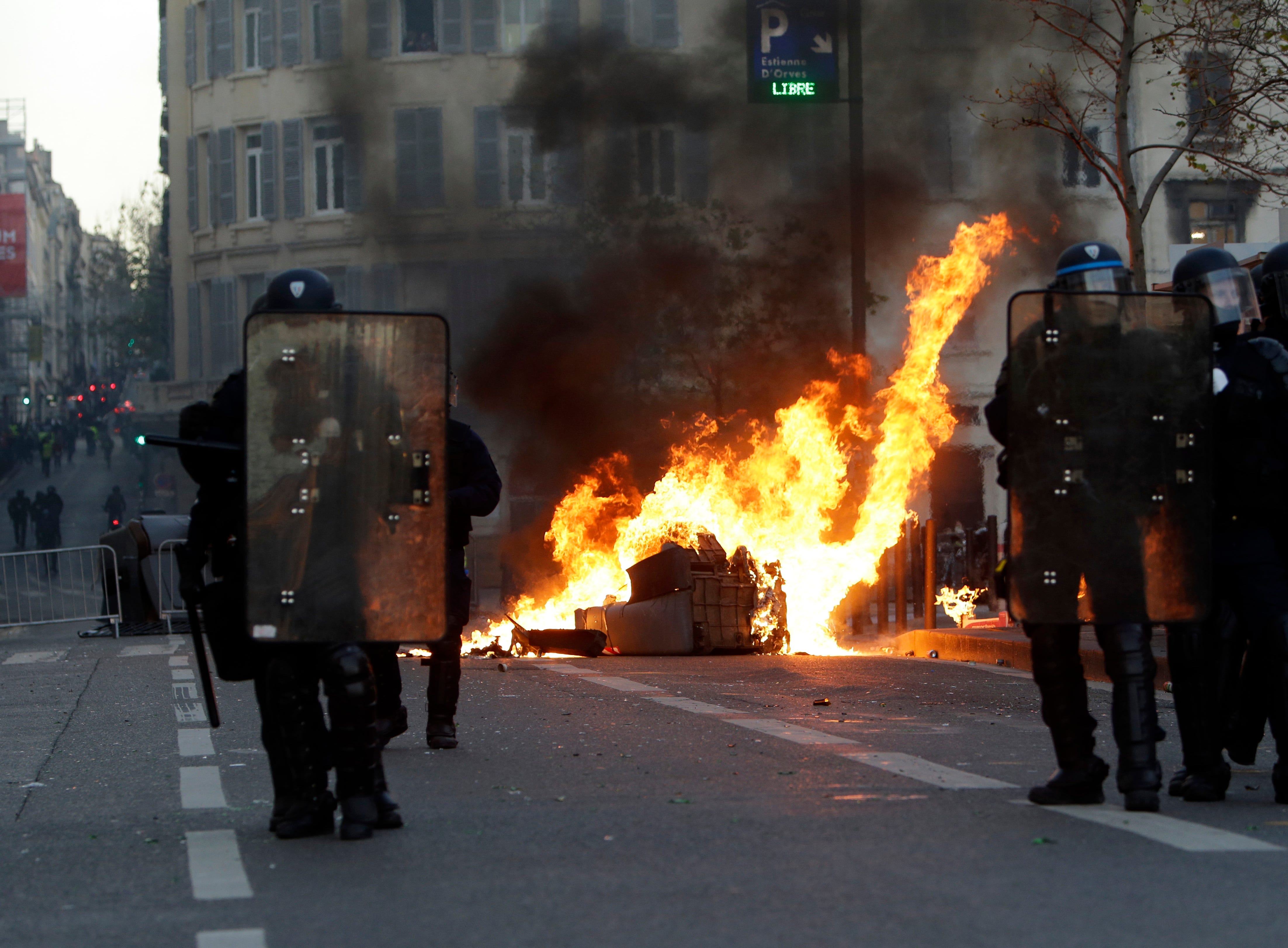 Riot police officer stand in front a burning trash bin during clashes, Saturday, Dec. 8, 2018, in Marseille, southern France. French riot police fired tear gas and water cannon in Paris on Saturday, trying to stop thousands of yellow-vested protesters from converging on the presidential palace to express their anger at high taxes and French President Emmanuel Macron.