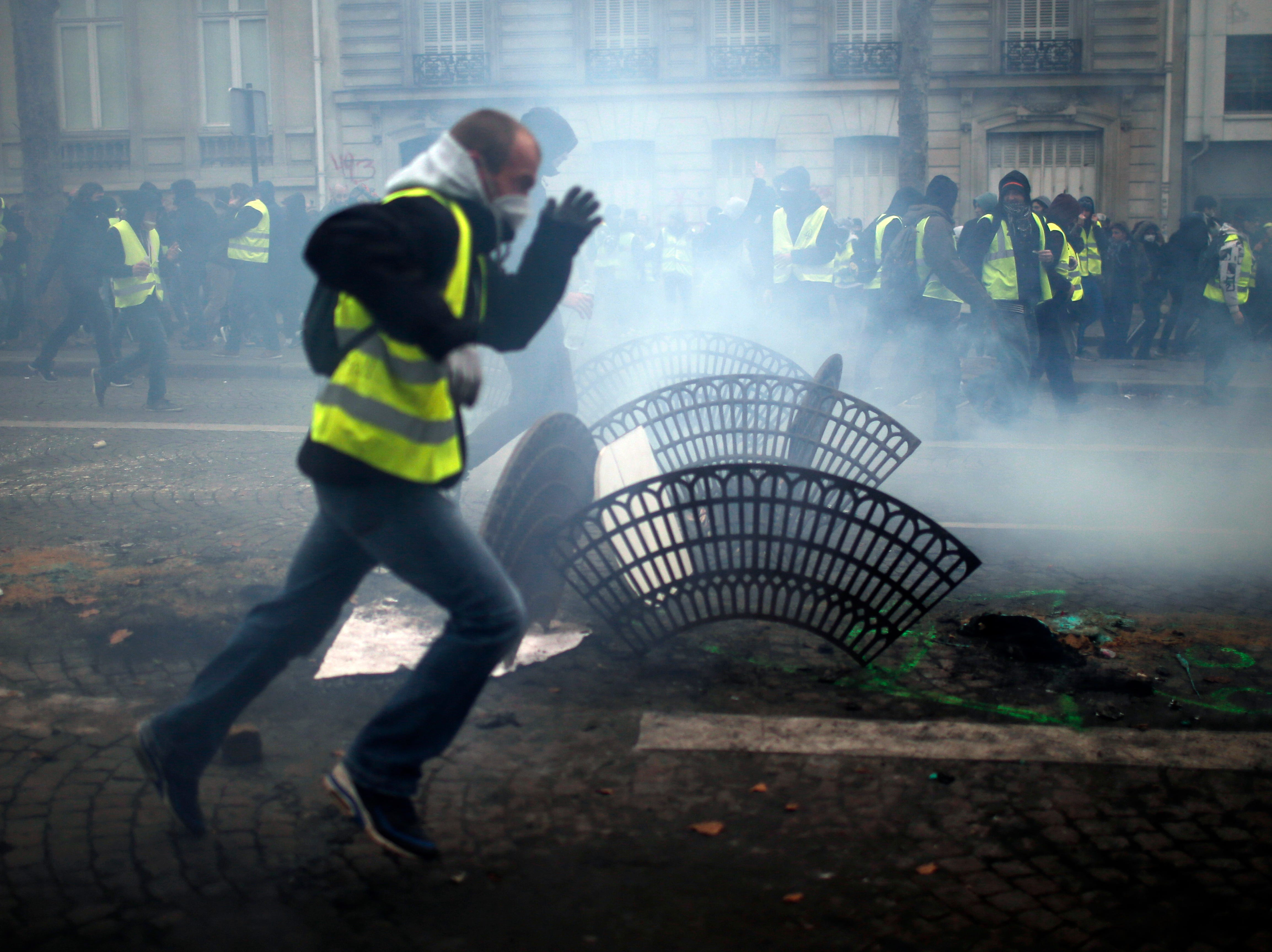 Demonstrators run away during clashes Saturday, Dec. 8, 2018, in Paris. Crowds of yellow-vested protesters angry at President Emmanuel Macron and France's high taxes tried to converge on the presidential palace Saturday, some scuffling with police firing tear gas, amid exceptional security measures aimed at preventing a repeat of last week's rioting.