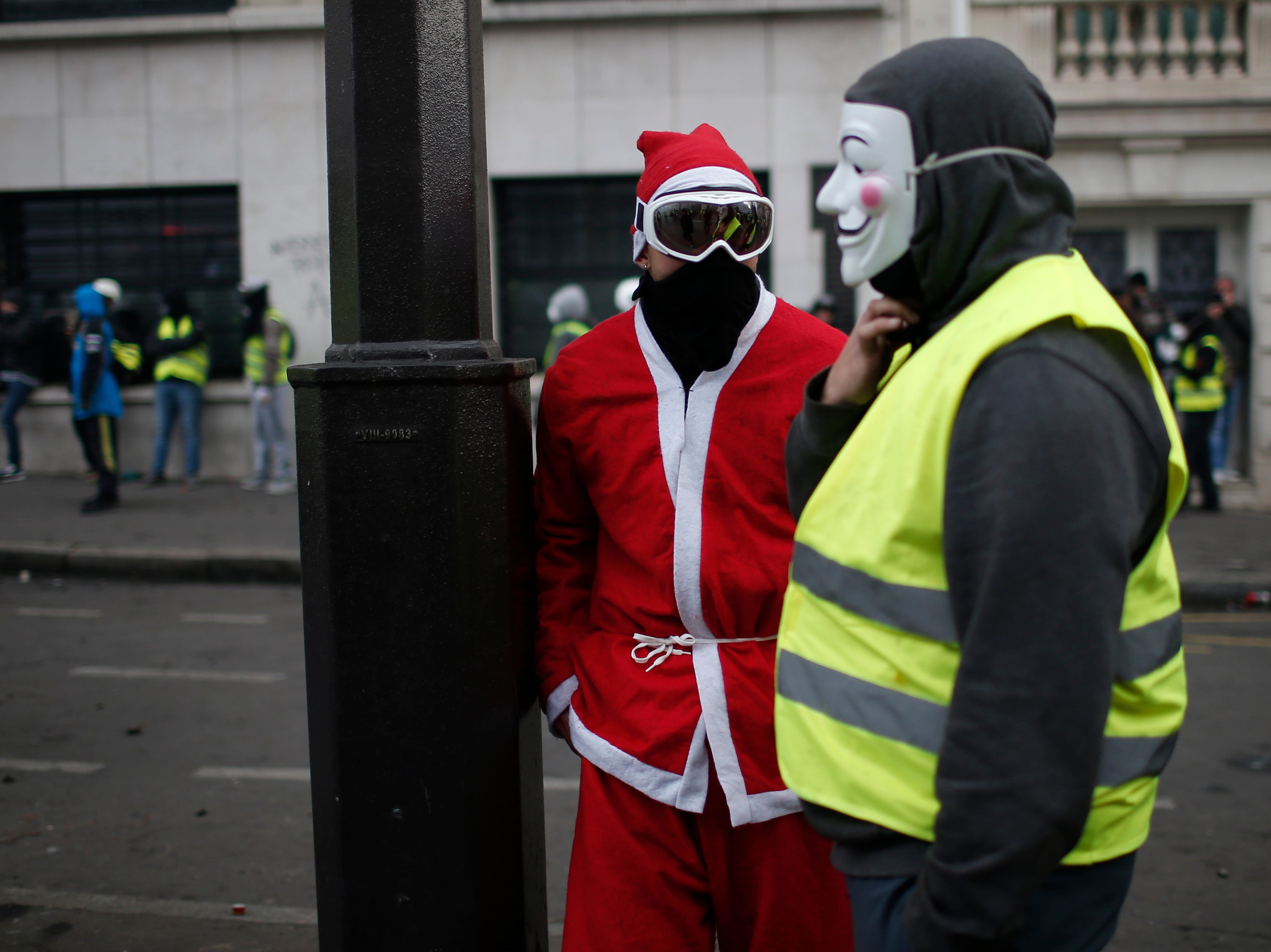Demonstrators, one dressed like a Santa Claus, talk during clashes Saturday, Dec. 8, 2018, in Paris. Crowds of yellow-vested protesters angry at President Emmanuel Macron and France's high taxes tried to converge on the presidential palace Saturday, some scuffling with police firing tear gas, amid exceptional security measures aimed at preventing a repeat of last week's rioting.