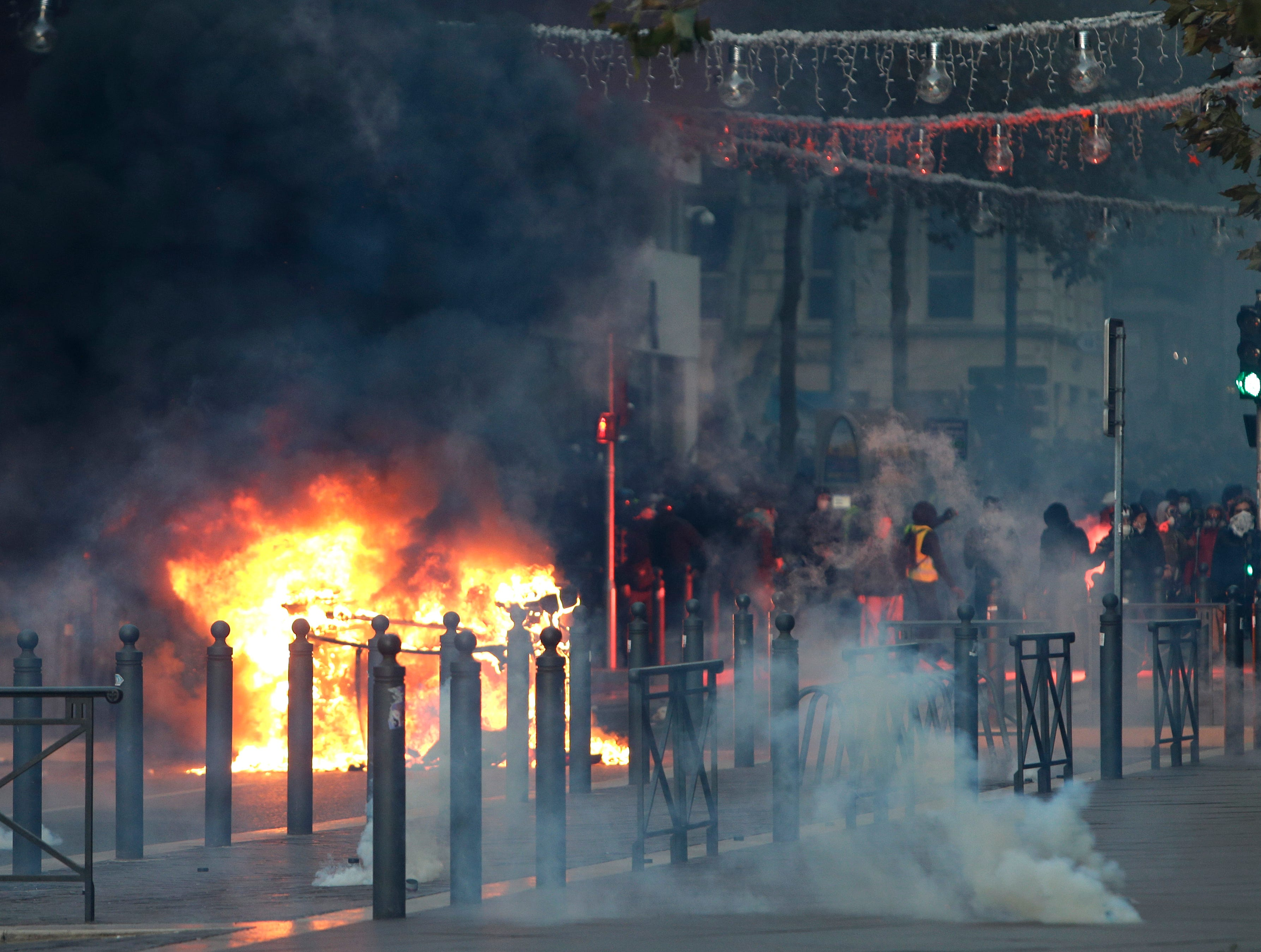 Demonstrators stand behind a burning car during clashes, Saturday, Dec. 8, 2018, in Marseille, southern France. French riot police fired tear gas and water cannon in Paris on Saturday, trying to stop thousands of yellow-vested protesters from converging on the presidential palace to express their anger at high taxes and French President Emmanuel Macron.