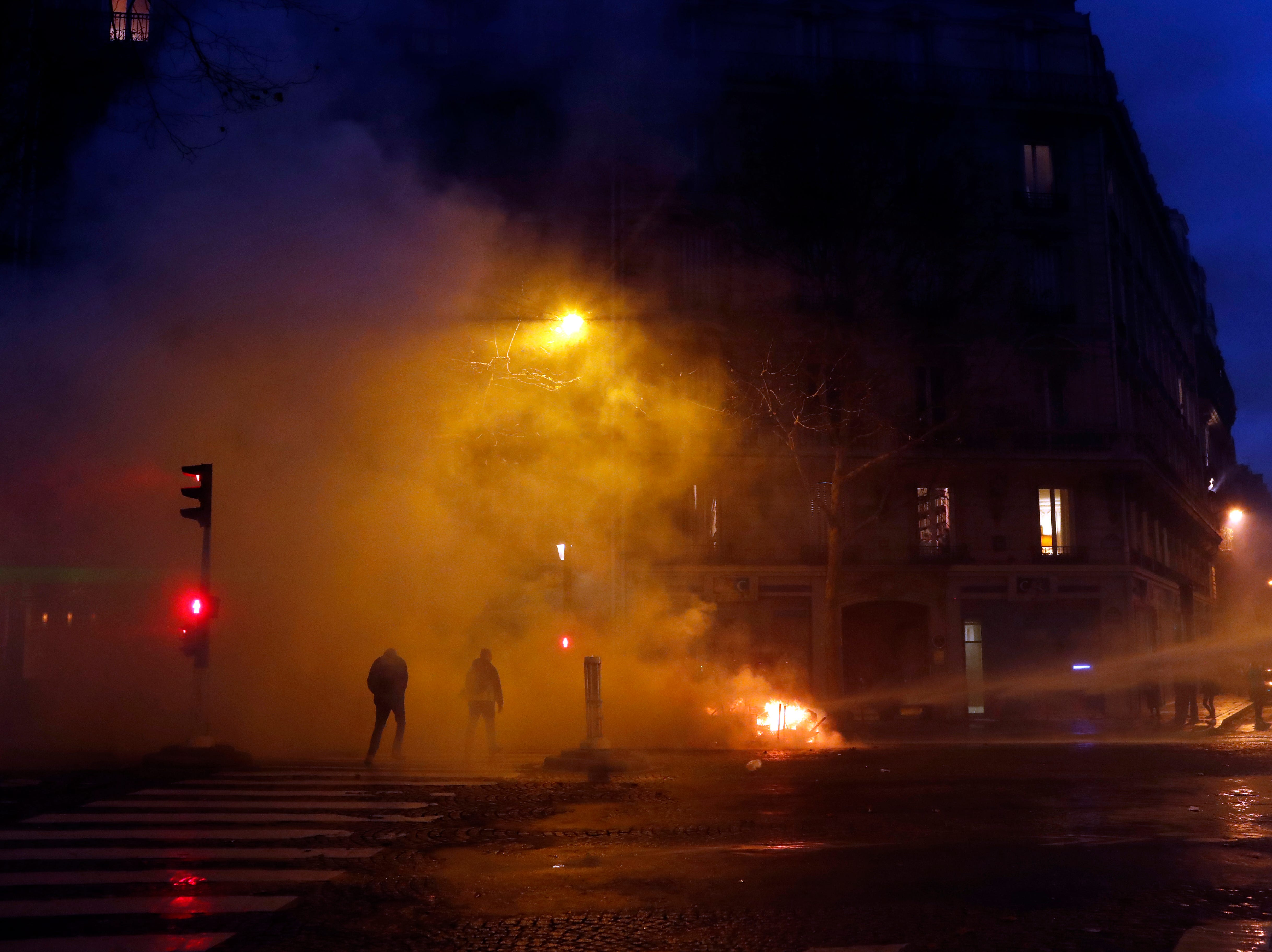 Demonstrators walk away from a cloud of tear gas fired by the police during an anti-government protest, in Paris, France, Saturday, Dec. 8, 2018. Crowds of protesters angry at President Emmanuel Macron and France's high taxes tried to converge on the presidential palace Saturday, some scuffling with police firing tear gas, amid exceptional security measures aimed at preventing a repeat of last week's rioting.