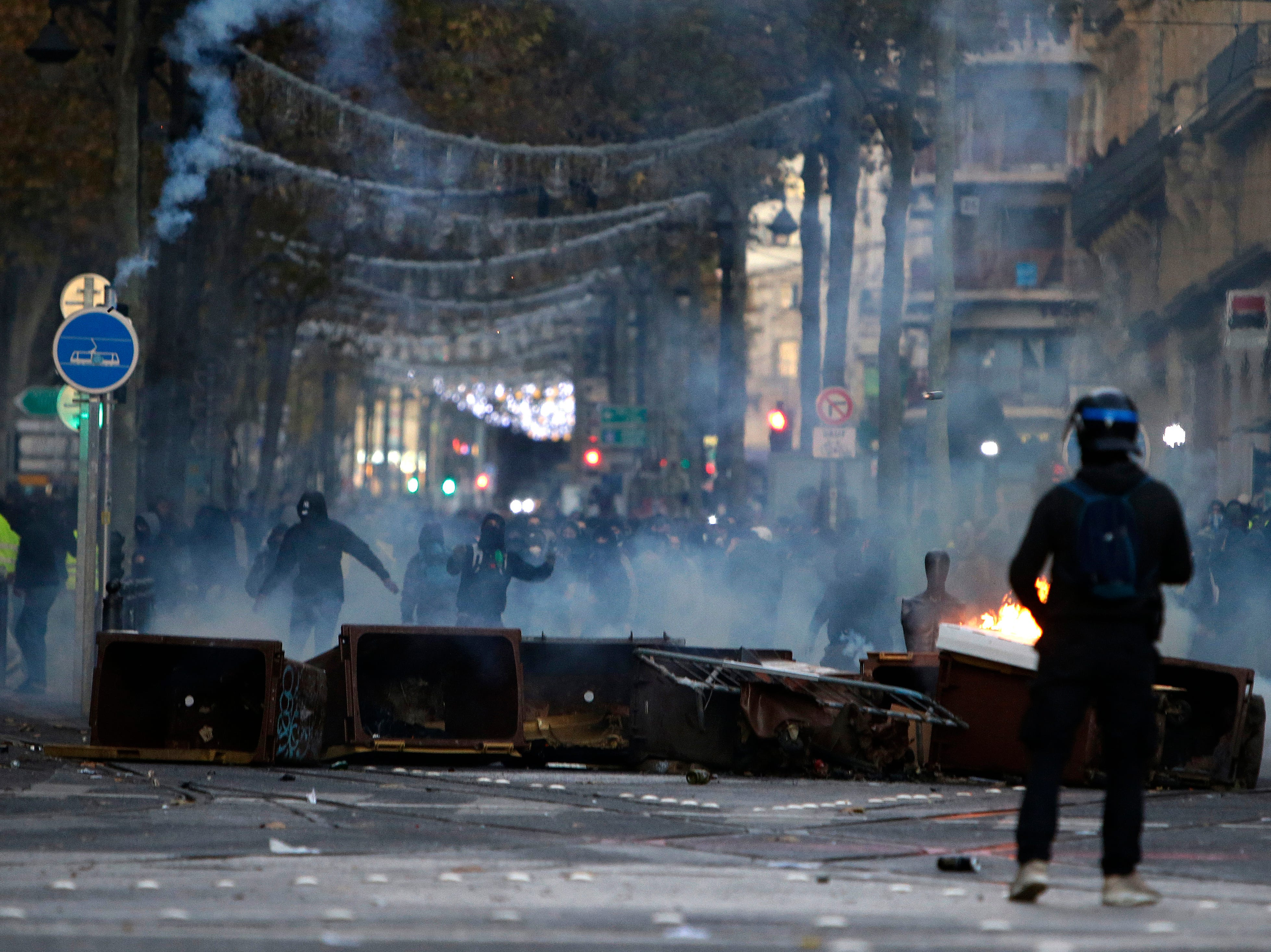 Demonstrators stand behind a burning barricade during clashes, Saturday, Dec. 8, 2018, in Marseille, southern France. The rumble of armored police trucks and the hiss of tear gas filled central Paris on Saturday, as French riot police fought to contain thousands of yellow-vested protesters venting their anger against the government in a movement that has grown more violent by the week.