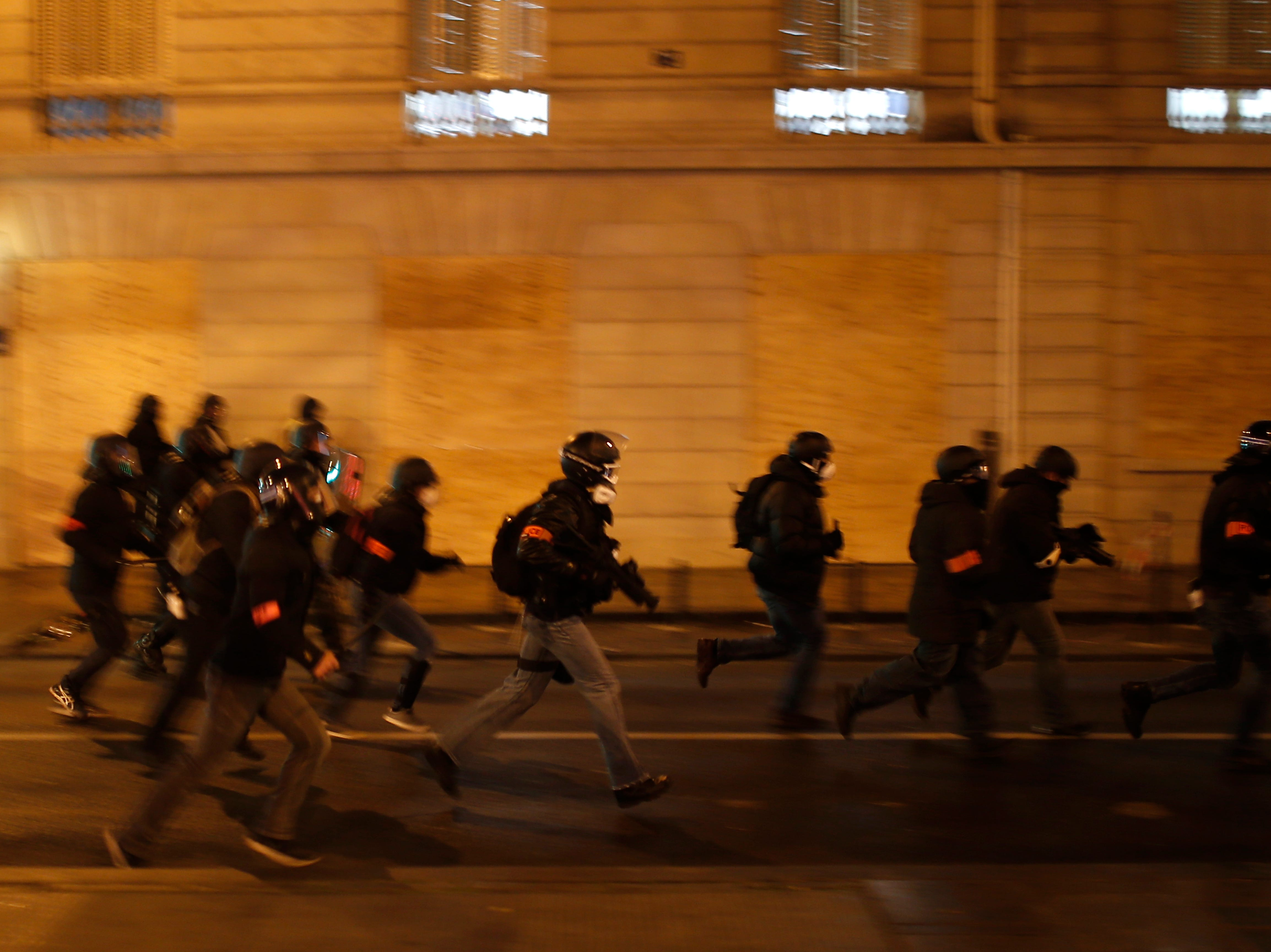French riot police officers charge during clashes Saturday, Dec. 8, 2018, in Paris. Crowds of yellow-vested protesters angry at President Emmanuel Macron and France's high taxes tried to converge on the presidential palace Saturday, some scuffling with police firing tear gas, amid exceptional security measures aimed at preventing a repeat of last week's rioting.