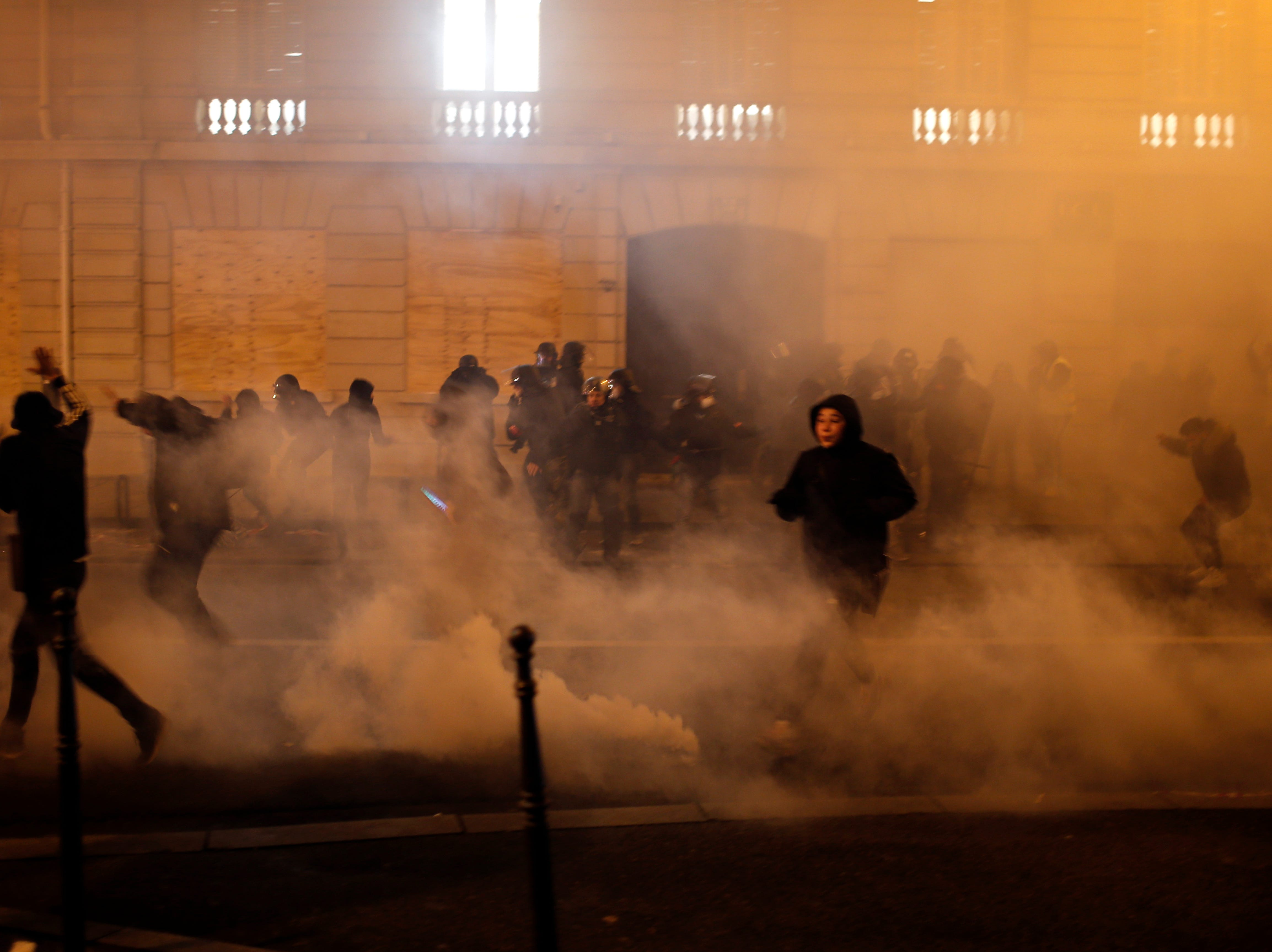 Demonstrators run away to avoid tear gas during clashes Saturday, Dec. 8, 2018, in Paris. Crowds of yellow-vested protesters angry at President Emmanuel Macron and France's high taxes tried to converge on the presidential palace Saturday, some scuffling with police firing tear gas, amid exceptional security measures aimed at preventing a repeat of last week's rioting.