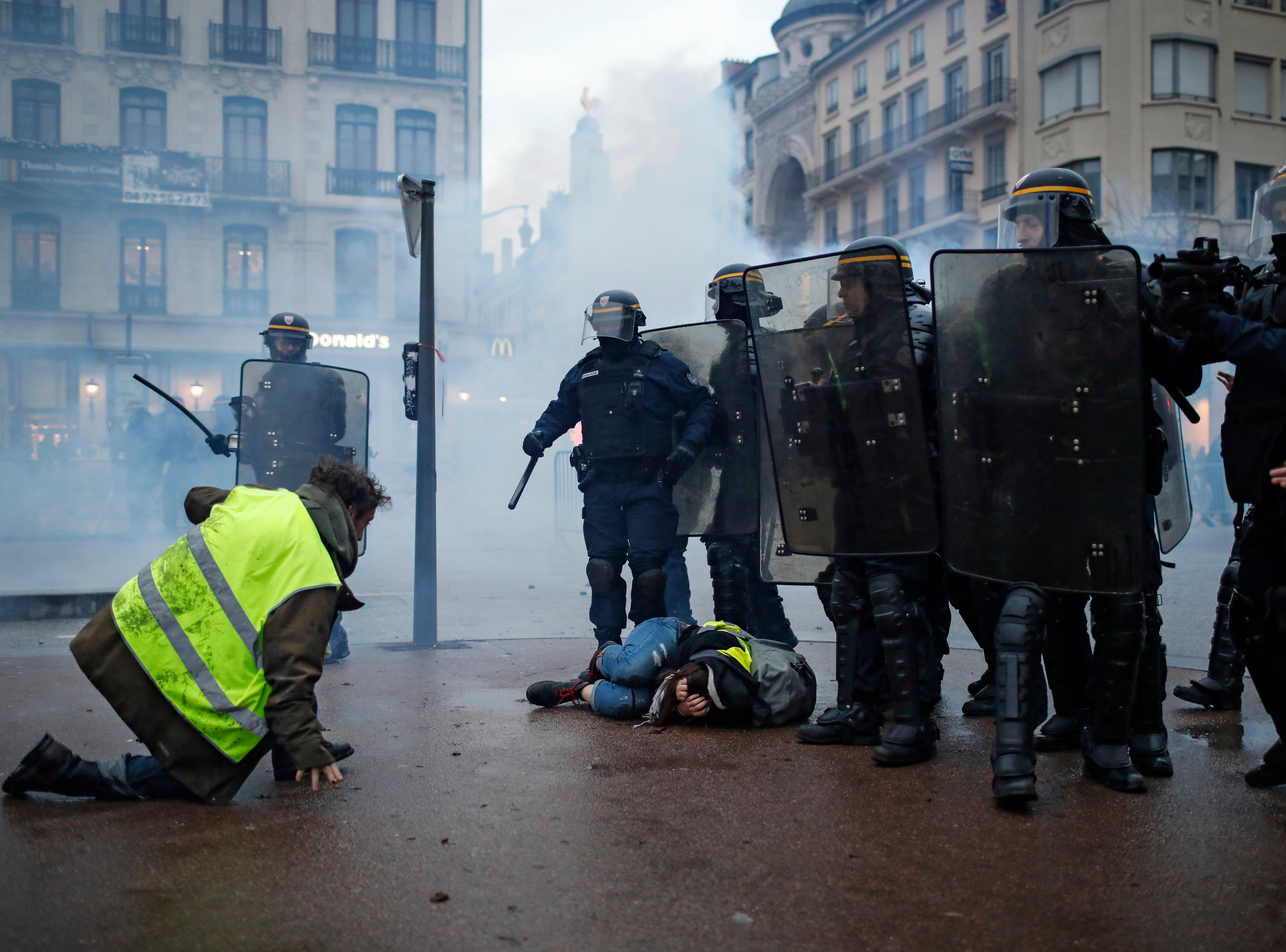 Police officers clash with demonstrators in Lyon, central France, Saturday, Dec. 8, 2018. The grassroots movement began as resistance against a rise in taxes for diesel and gasoline, but quickly expanded to encompass frustration at stagnant incomes and the growing cost of living.